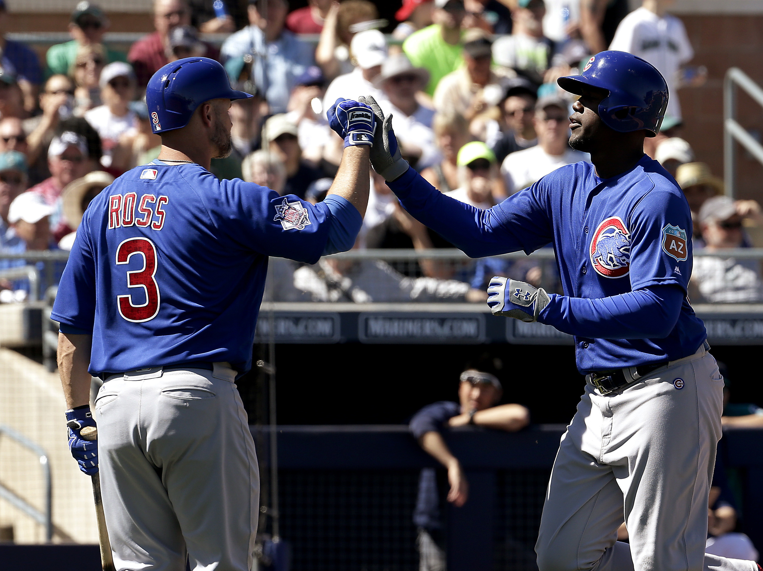 Chicago Cubs' Jorge Soler, right, celebrates with David Ross (3) after hitting a solo home run during the second inning of a spring training baseball game against the Seattle Mariners on Thursday, March 10, 2016, in Peoria, Ariz. (AP Photo/Charlie Riedel)