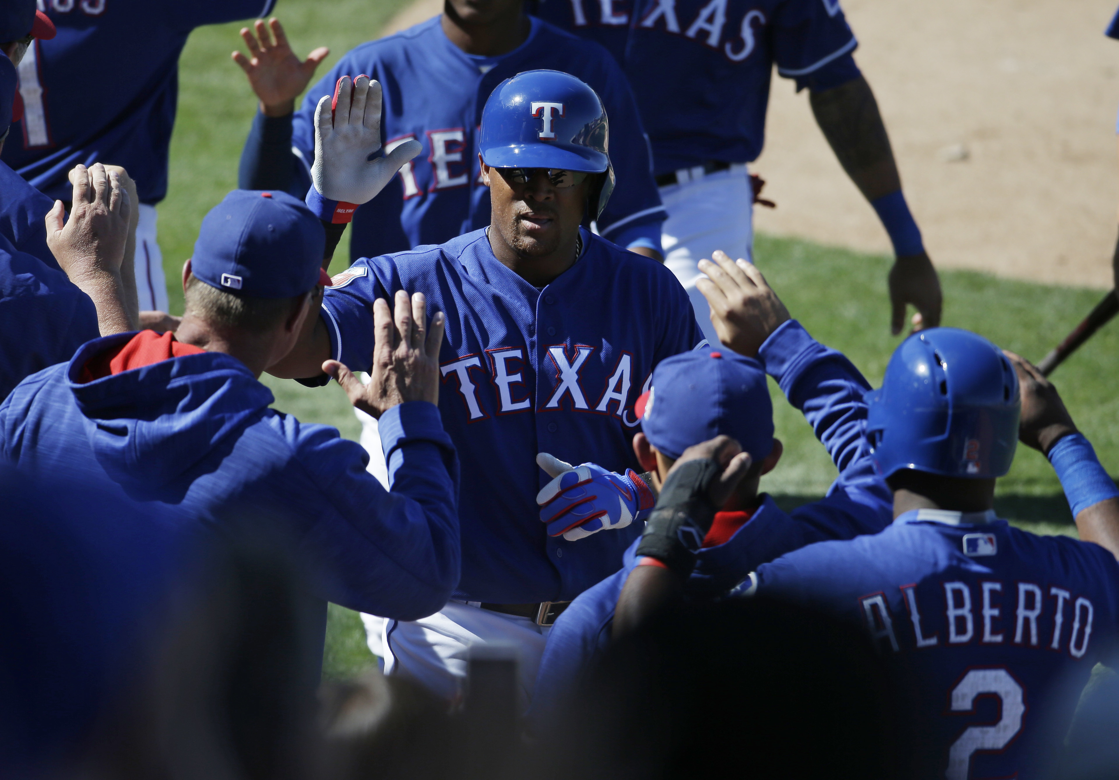 Texas Rangers' Adrian Beltre, center, celebrates with teammates after hitting a three-run home run inning of a spring training baseball game against the Oakland Athletics on Saturday, March 12, 2016, in Surprise, Ariz. (AP Photo/Darron Cummings)