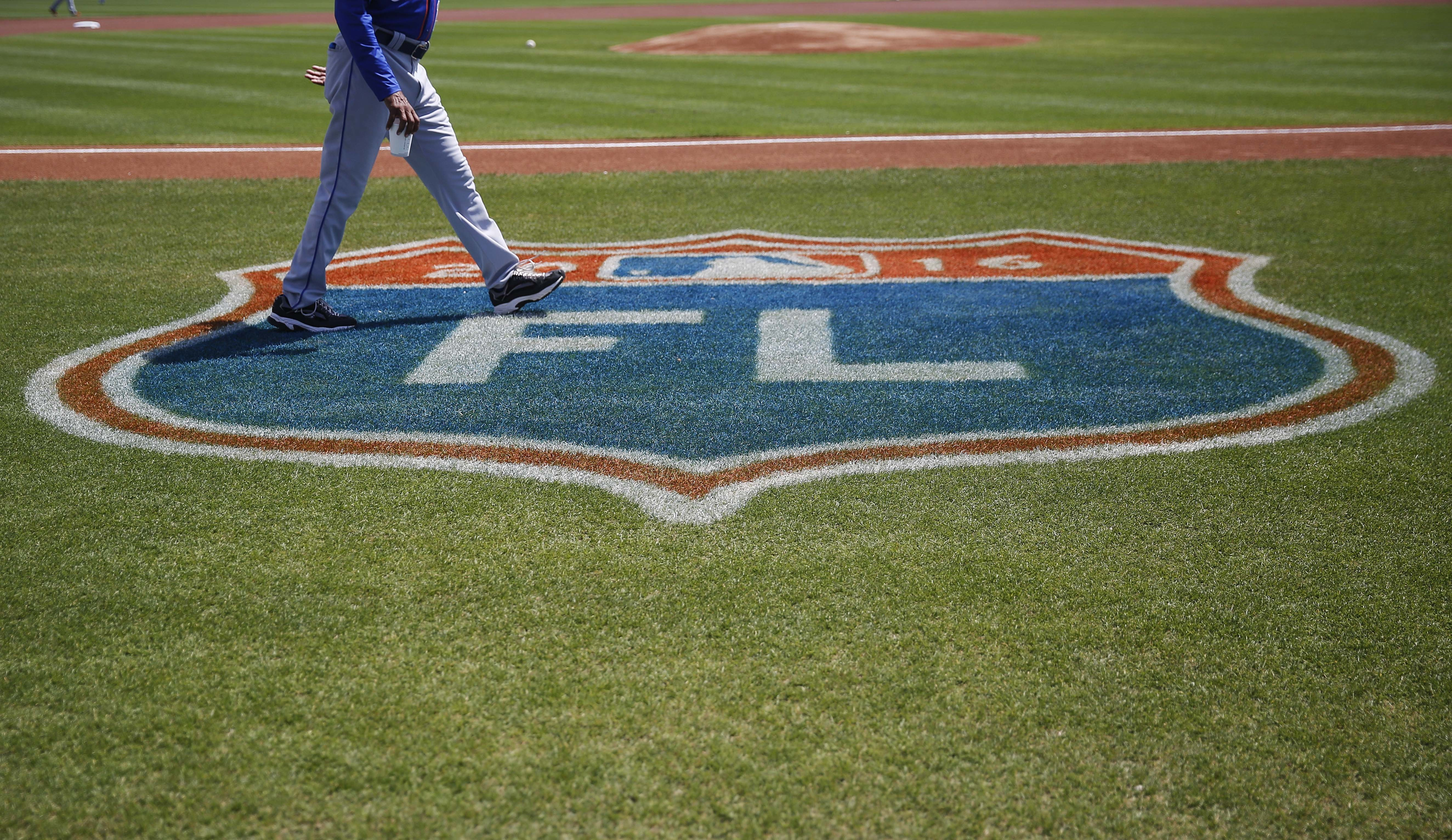 New York Mets first base coach Tom Goodwin walks onto the baseball field before an exhibition spring training baseball game against the Miami Marlins, Tuesday, March 15, 2016, in Jupiter, Fla. (AP Photo/Brynn Anderson)