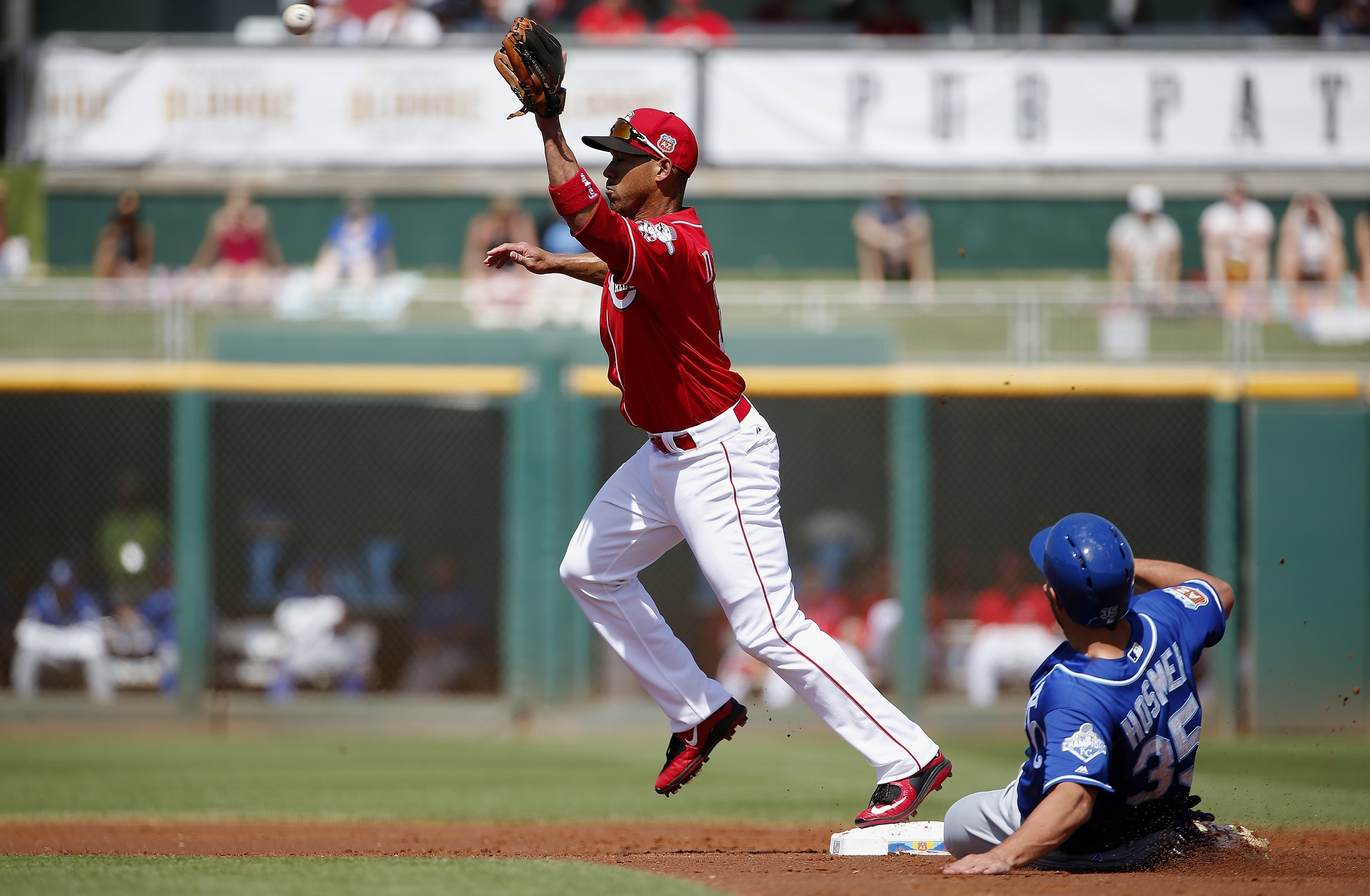 Cincinnati Reds' Ivan De Jesus, left, reaches out to make a catch to force out Kansas City Royals' Eric Hosmer (35) at second base during the first inning of a spring training baseball game, Tuesday, March 15, 2016, in Goodyear, Ariz. (AP Photo/Ross D. Fr