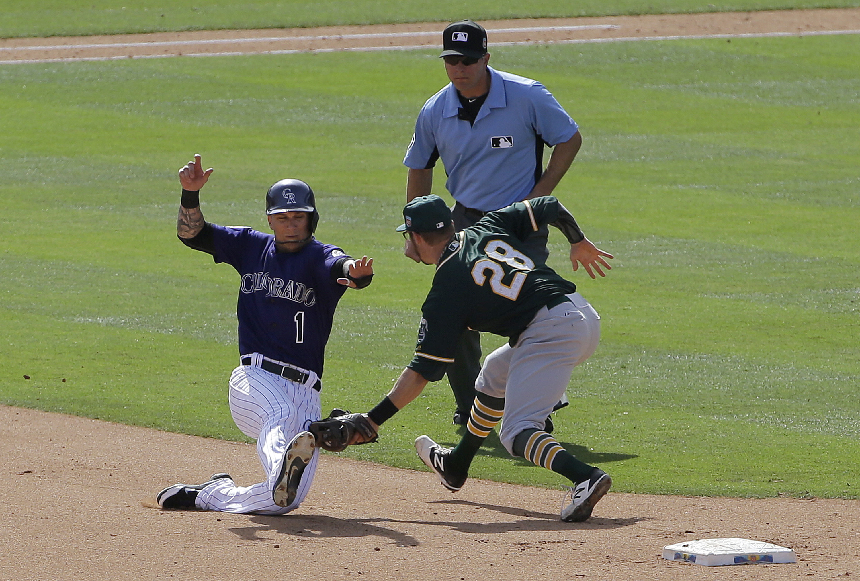 Colorado Rockies' Brandon Barnes (1) is tagged out by Oakland Athletics second baseman Eric Sogard (28) trying to steal second base during the fourth inning of a spring training baseball game in Scottsdale, Ariz., Tuesday, March 15, 2016. (AP Photo/Jeff C