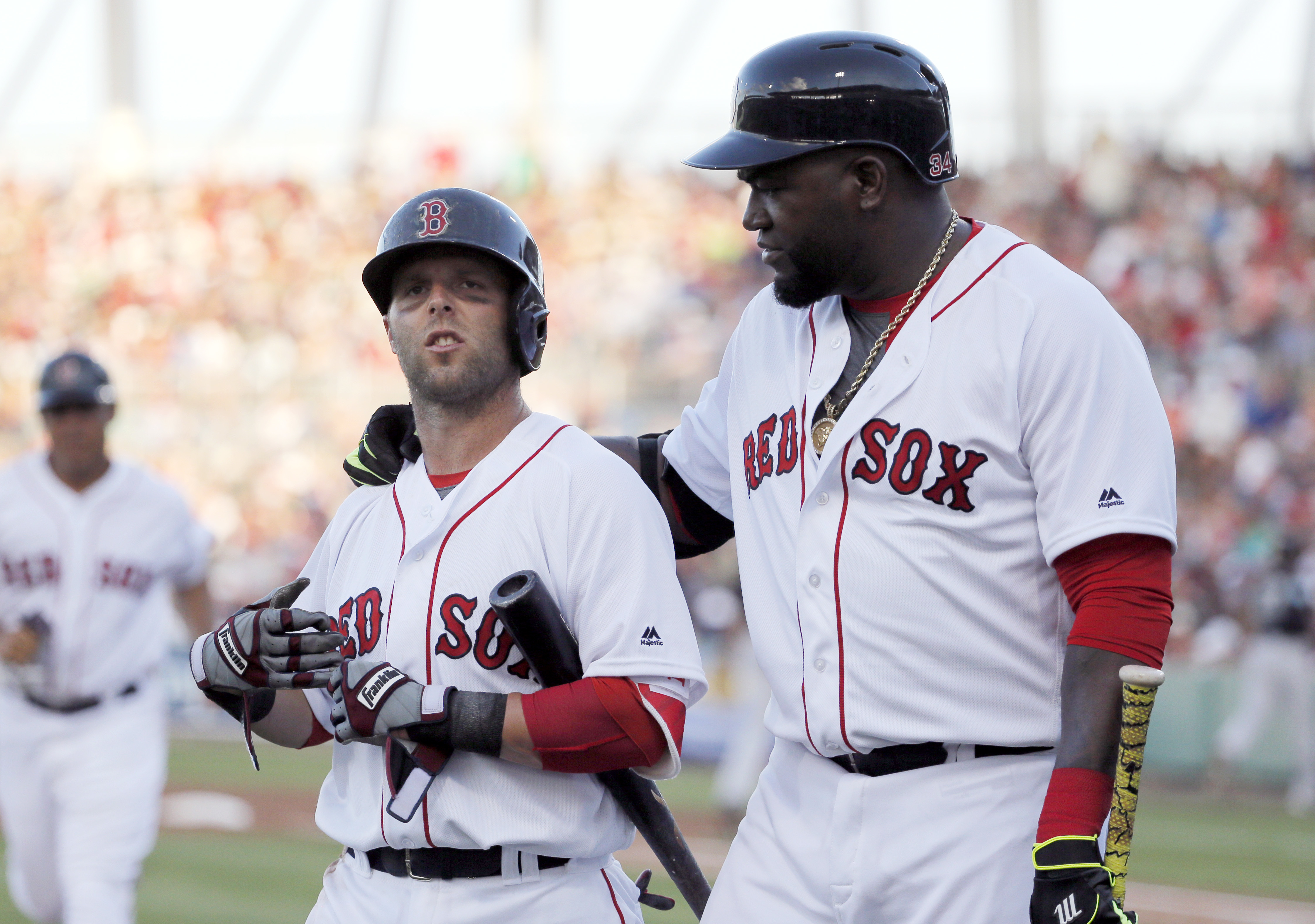 Boston Red Sox's David Ortiz, right, puts his arm around Dustin Pedroia (15) as the two walk back to the dugout after Pedroia struck against against pitches from New York Yankees' Ivan Nova in the third inning of a spring training baseball game, Tuesday,
