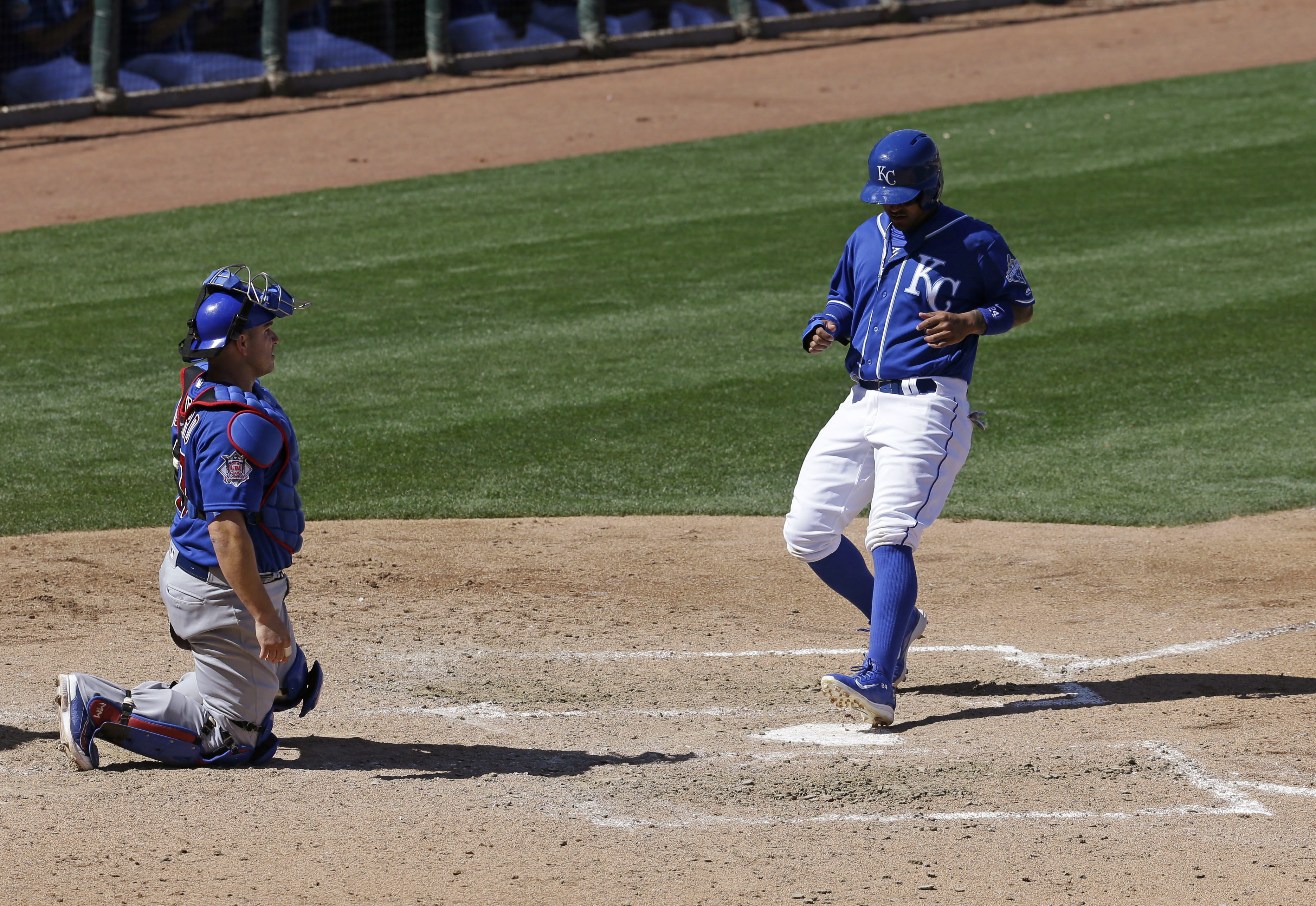 Kansas City Royals' Christian Colon scores in front of Chicago Cubs catcher Miguel Montero during the fifth inning of a spring training baseball game Wednesday, March 16, 2016, in Surprise, Ariz. (AP Photo/Darron Cummings)