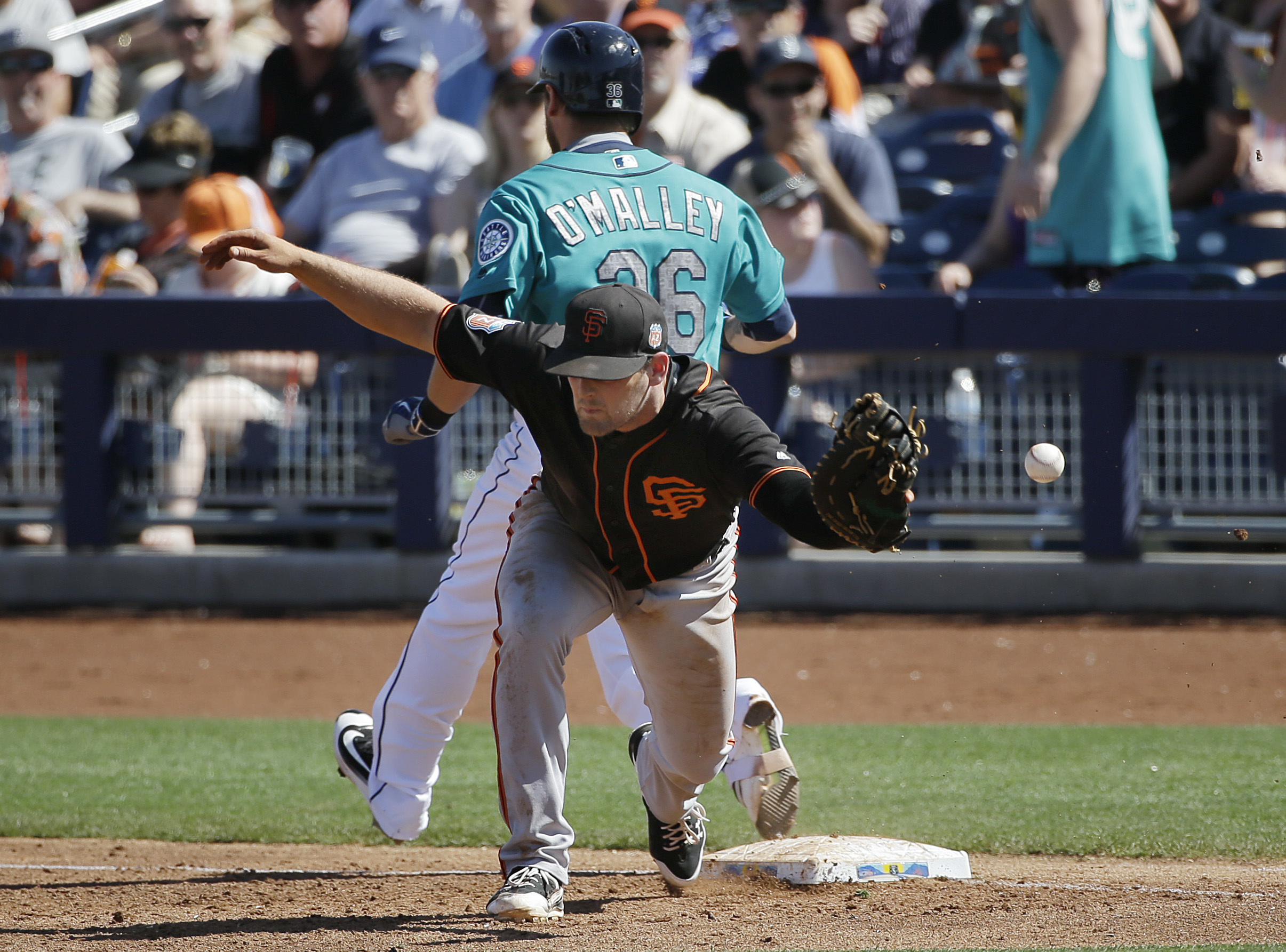 Seattle Mariners' Shawn O'Malley safely takes first base as San Francisco Giants first baseman Conor Gillaspie misses the throw from third baseman Kelby Tomlinson during the third inning of a spring training baseball game Wednesday, March 16, 2016, in Peo