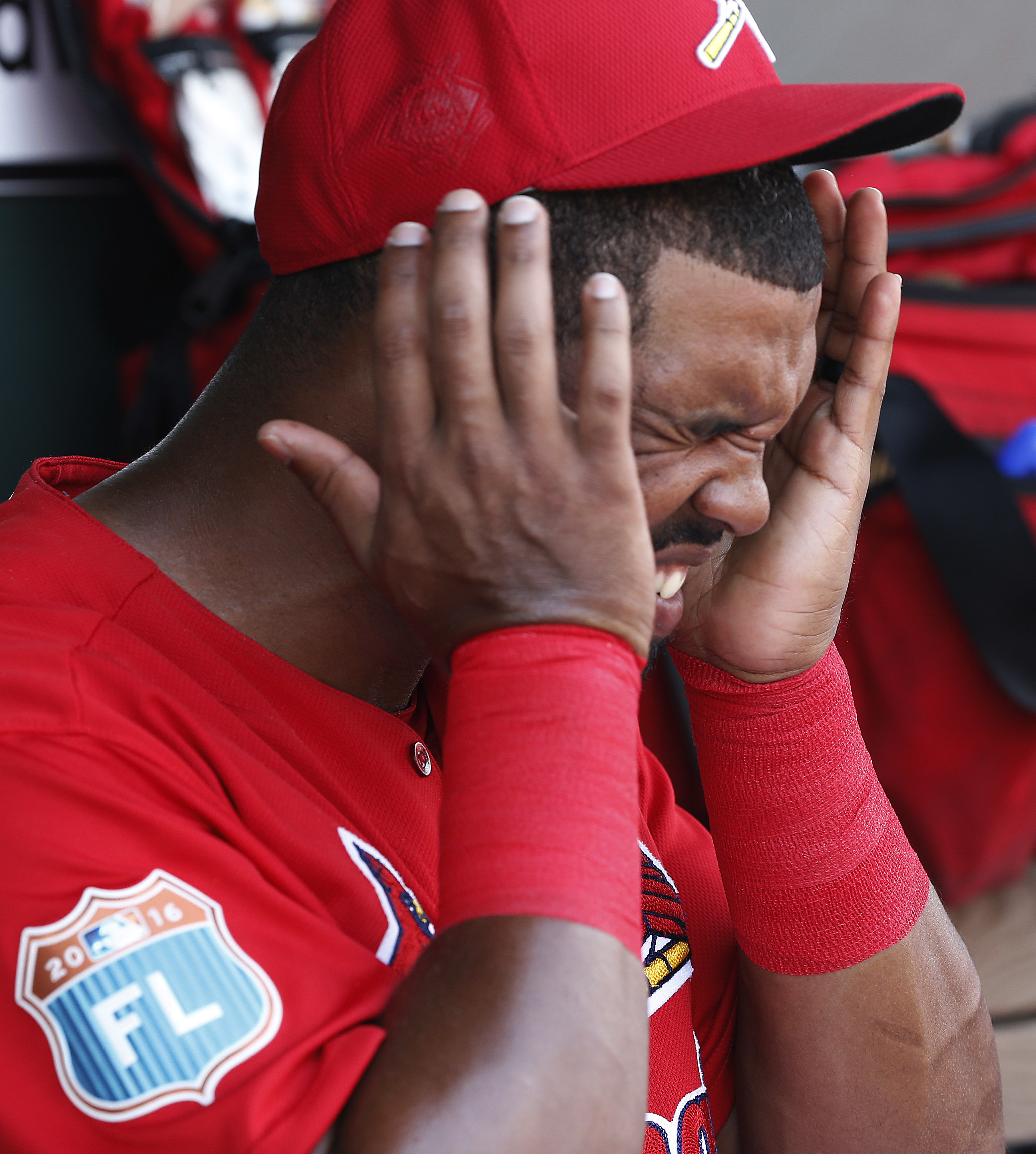 St. Louis Cardinals' Carlos Peguero, reacts to getting sunblock in his eyes in the dugout during the fourth inning of an exhibition spring training baseball game against the Detroit Tigers, Friday, March 18, 2016, in Jupiter, Fla. (AP Photo/Brynn Anderson