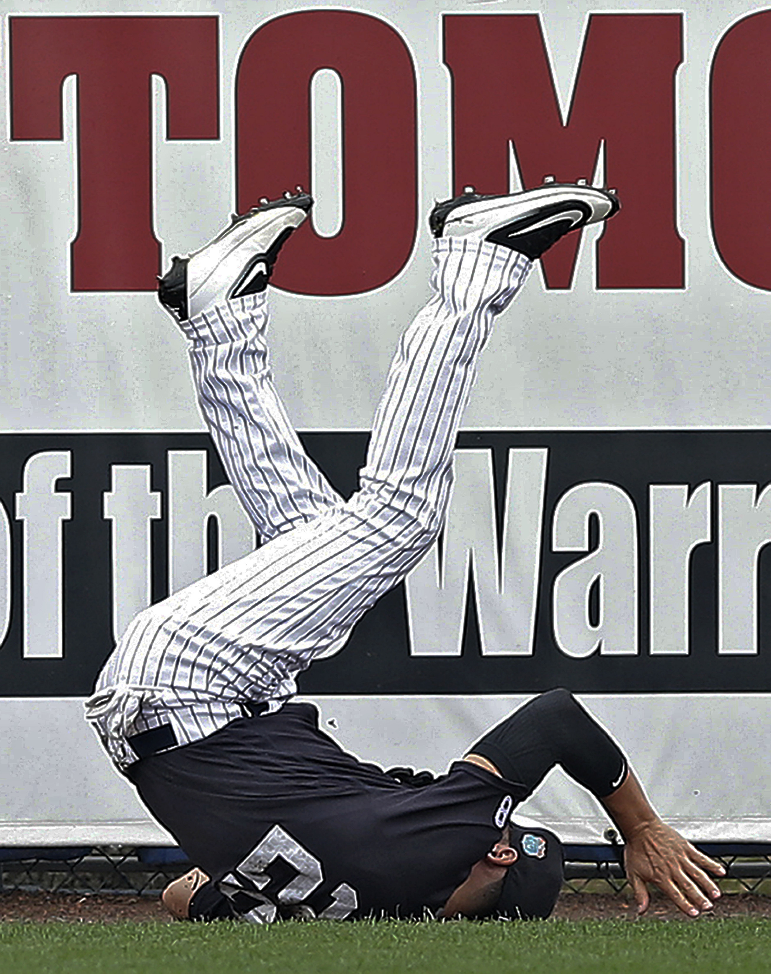 New York Yankees center fielder Jacoby Ellsbury flips over after making a diving catch on a fly ball by Atlanta Braves' Nick Swisher during the first inning of a spring training baseball game Saturday, March 19, 2016, in Tampa, Fla. (AP Photo/Chris O'Mear
