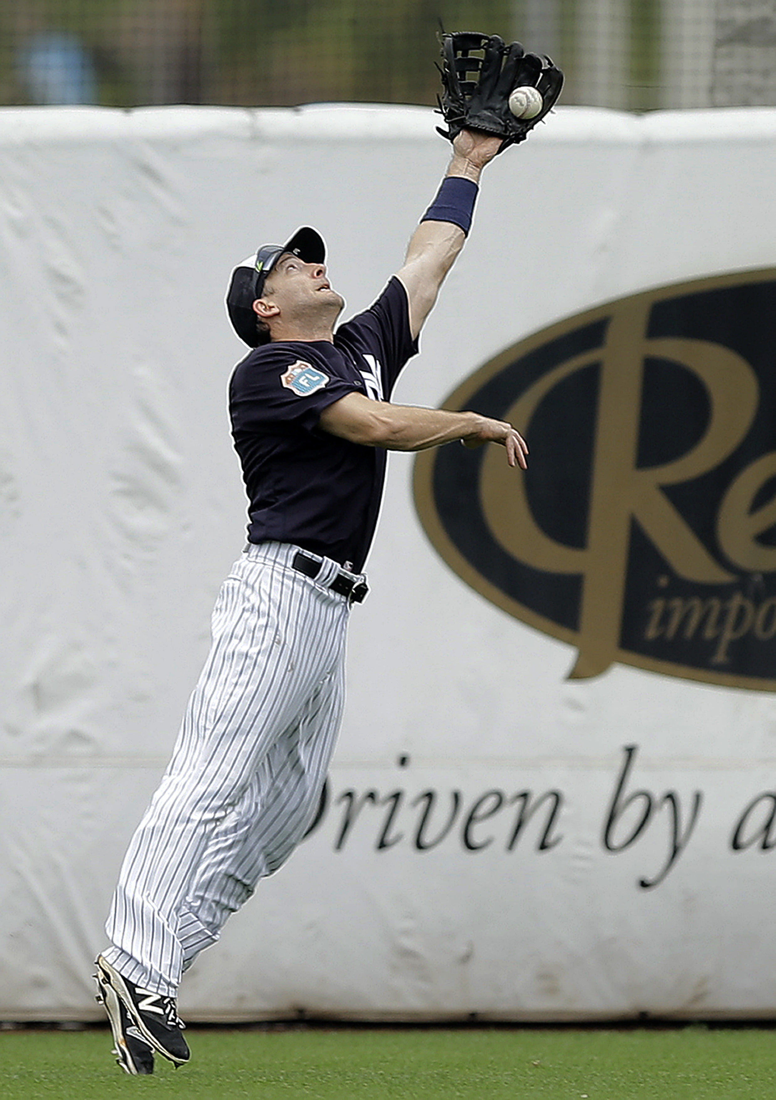 New York Yankees left fielder Chris Denorfia can't hang onto a double by Atlanta Braves' Hector Olivera during the fifth inning of a spring training baseball game Saturday, March 19, 2016, in Tampa, Fla. (AP Photo/Chris O'Meara)