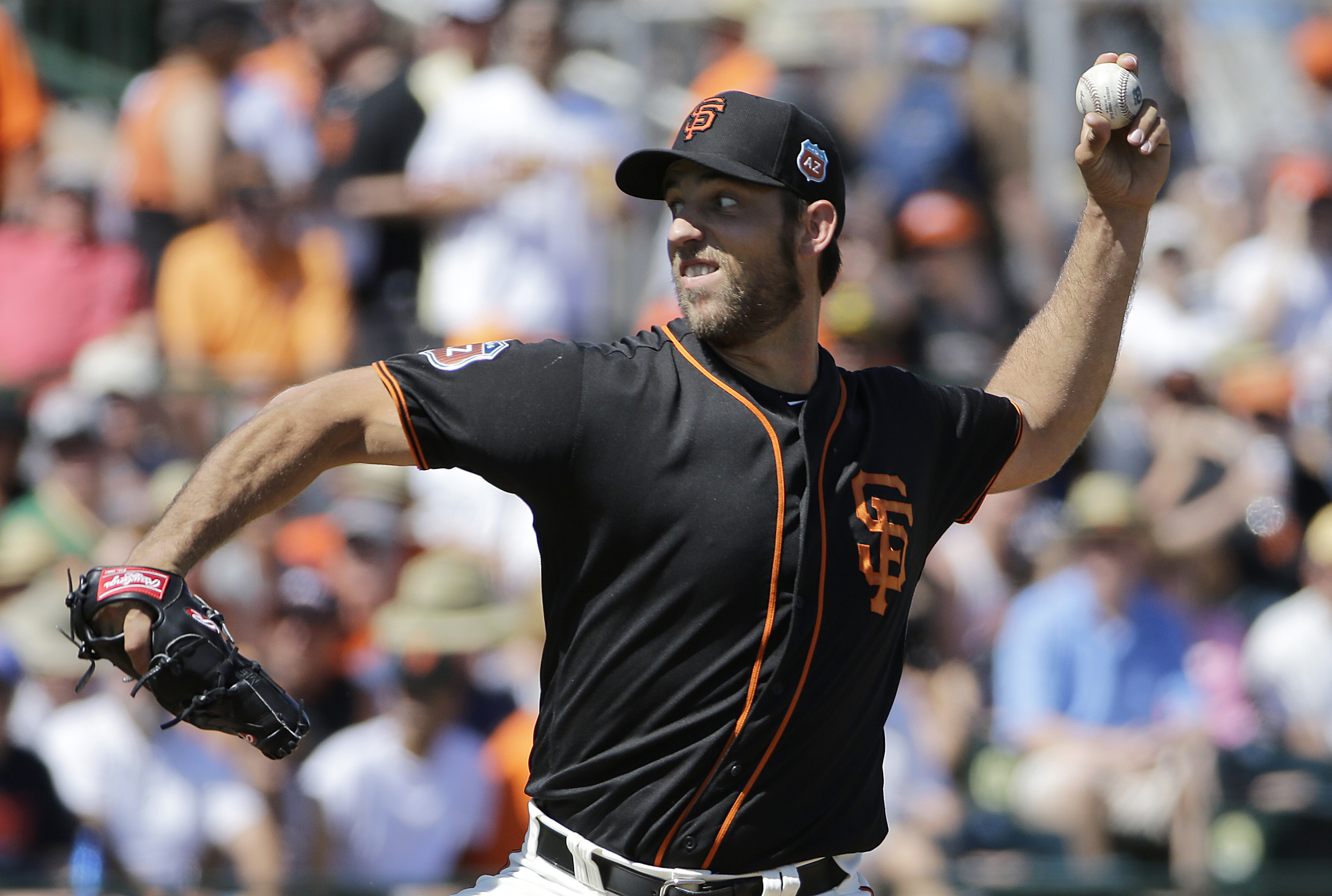 San Francisco Giants starting pitcher Madison Bumgarner throws during the first inning of a spring training baseball game against the Oakland Athletics in Scottsdale, Ariz., Saturday, March 19, 2016. (AP Photo/Jeff Chiu)
