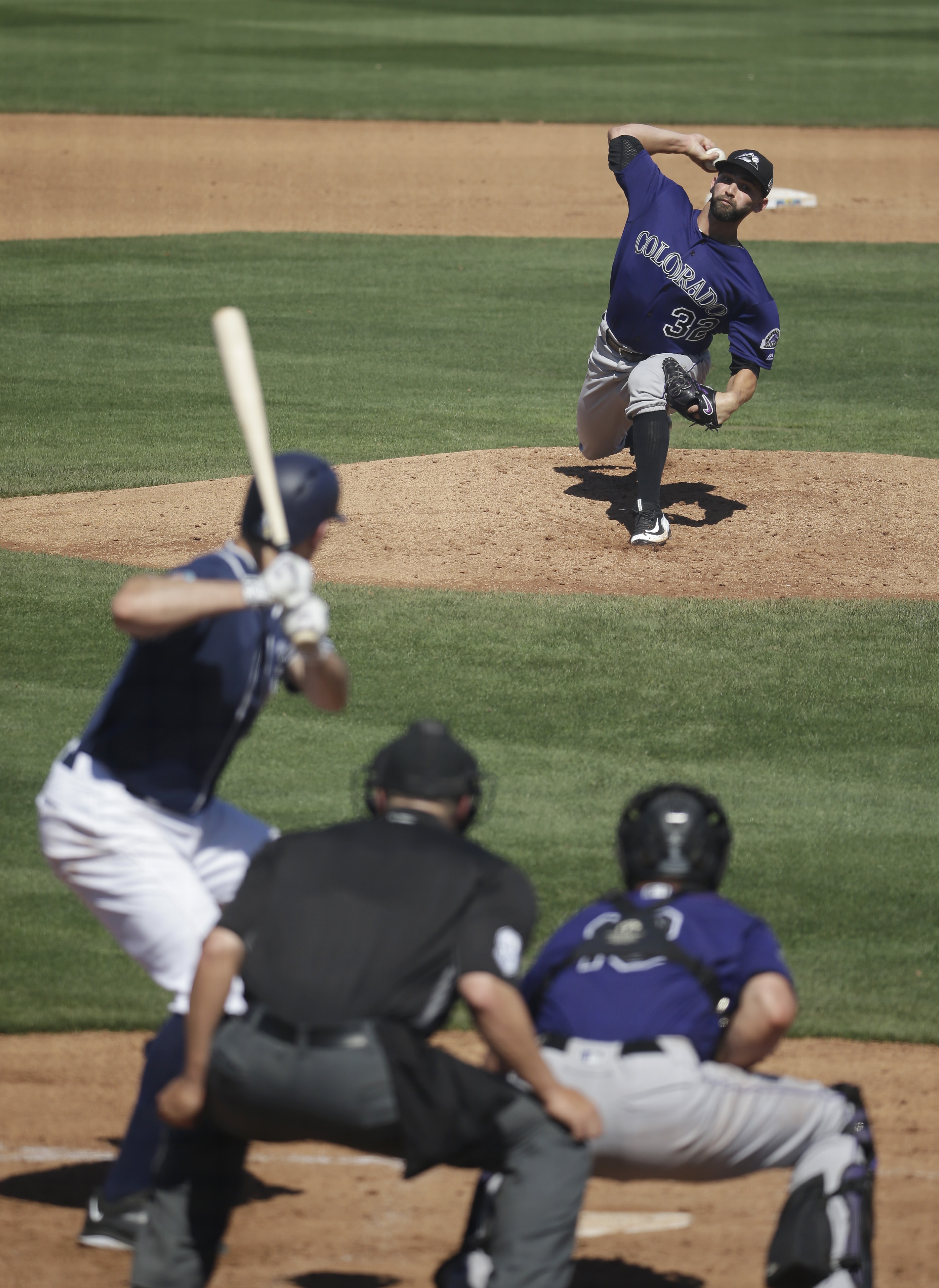 Colorado Rockies' Tyler Chatwood, top, throws during the fourth inning of a spring training baseball game against the San Diego Padres on Saturday, March 19, 2016, in Peoria, Ariz. (AP Photo/Darron Cummings)