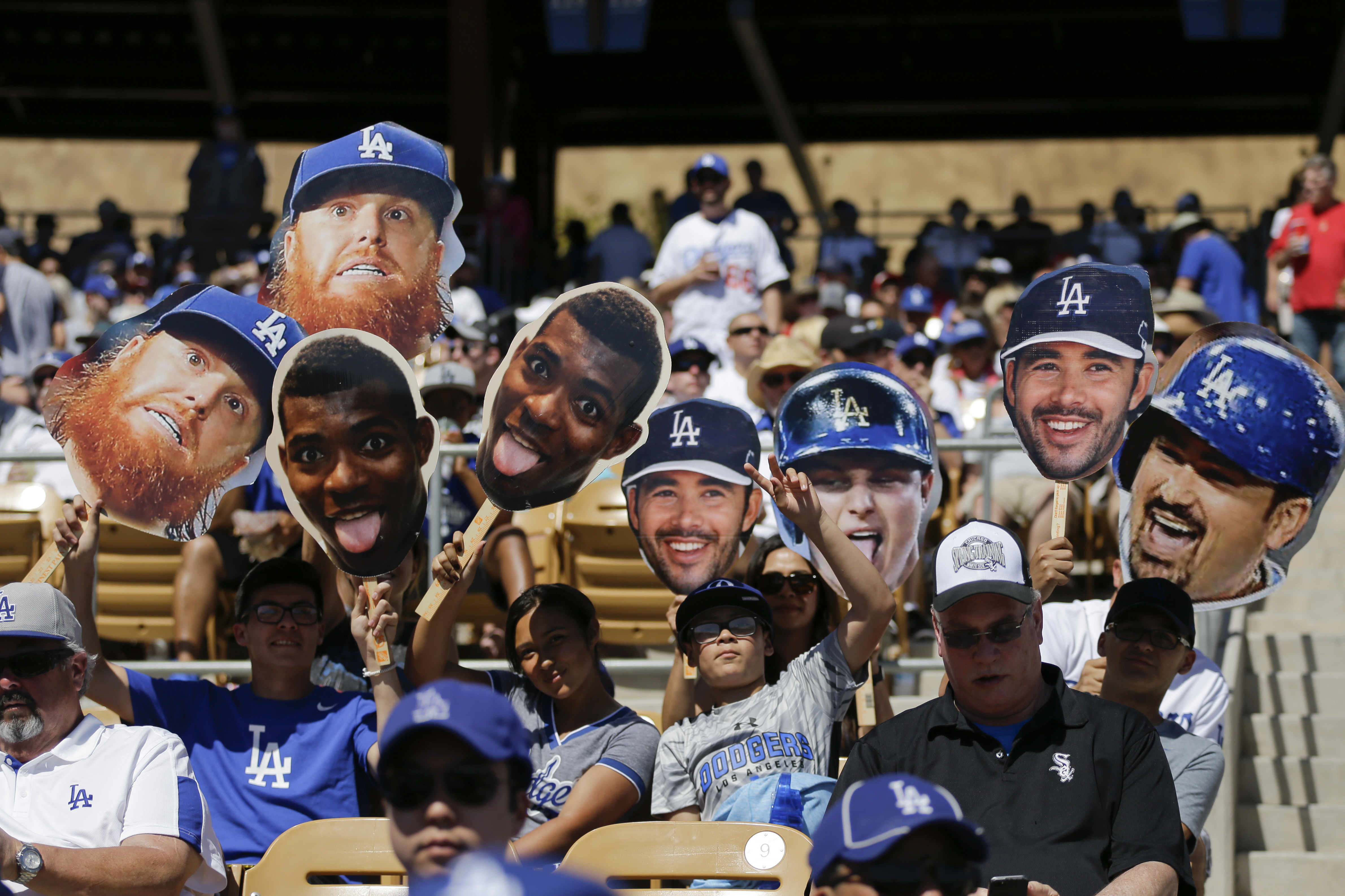 Fans cheer for the Los Angeles Dodgers while watching the team's spring training baseball game against the Chicago White Sox on Saturday, March 19, 2016, in Phoenix. (AP Photo/Jae C. Hong)