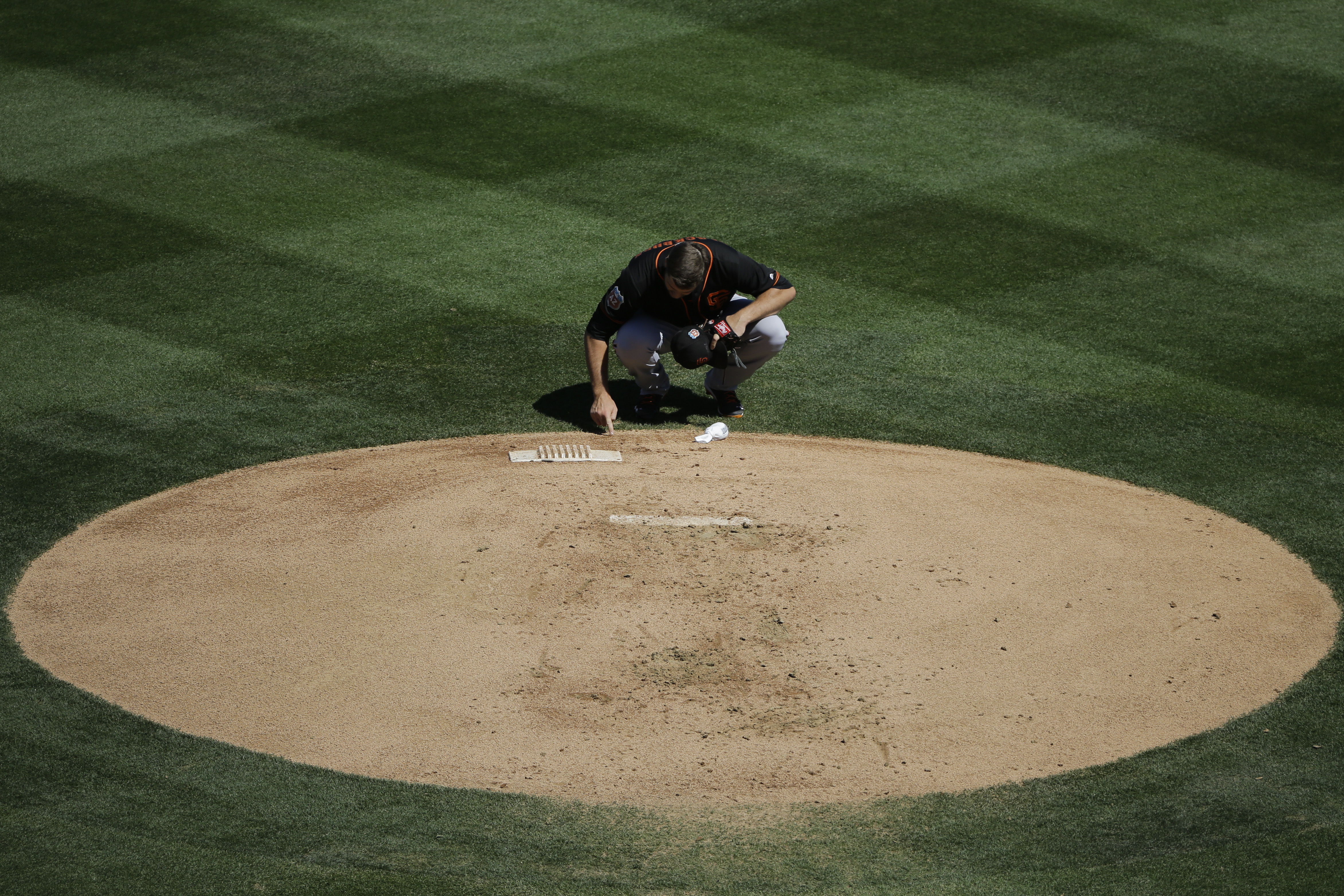 San Francisco Giants starting pitcher Clayton Blackburn writes on the mound before pitching against the Colorado Rockies at the start of the first inning of a spring training baseball game Sunday, March 20, 2016, in Scottsdale, Ariz. (AP Photo/Jae C. Hong