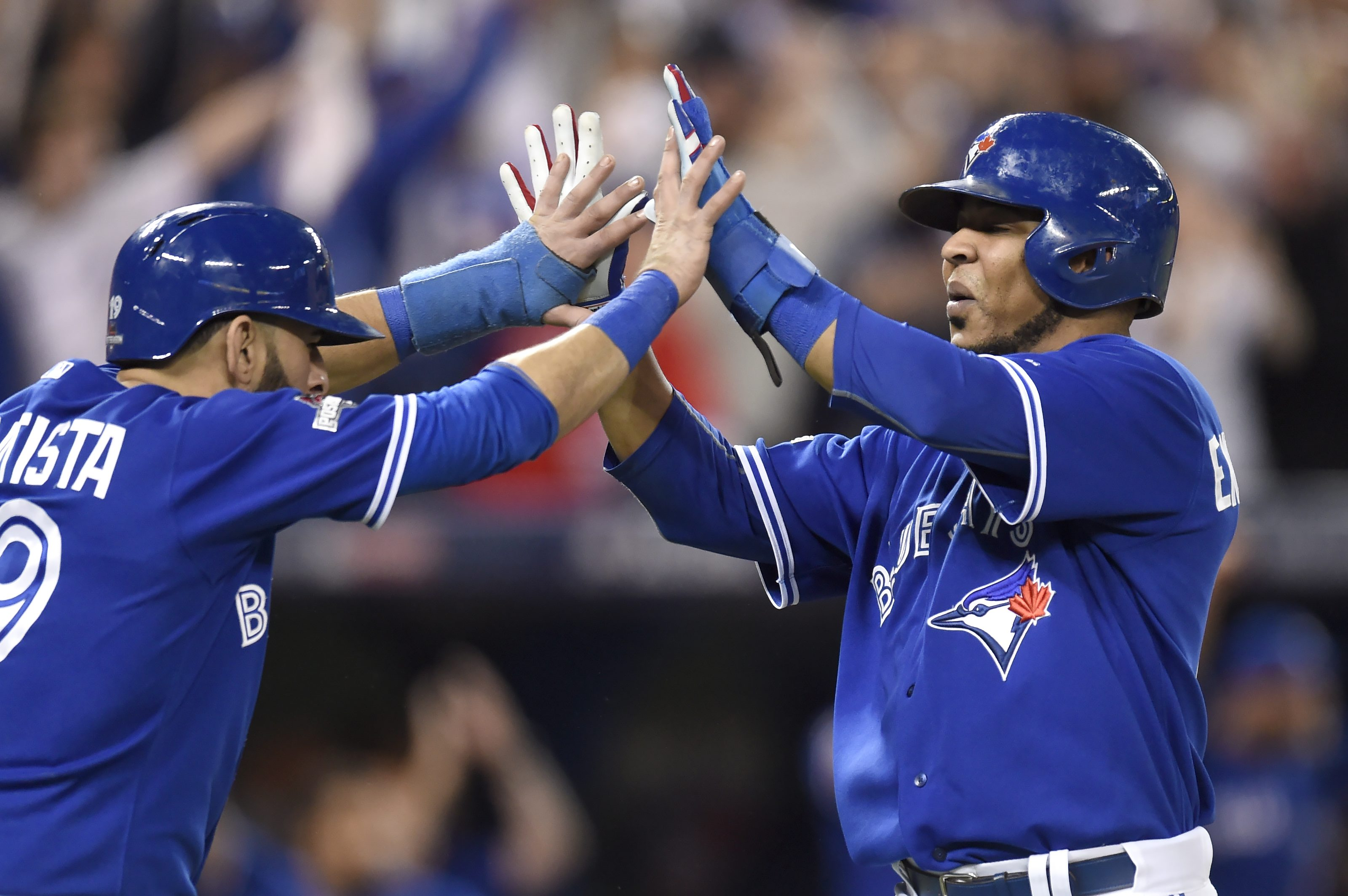FILE - In this Wednesday, Oct. 21, 2015 file photo, Toronto Blue Jays' Jose Bautista, left, and Edwin Encarnacion celebrate after scoring on a three-run double during Game 5 of baseball's American League Championship Series in Toronto. Bautista, a six-tim