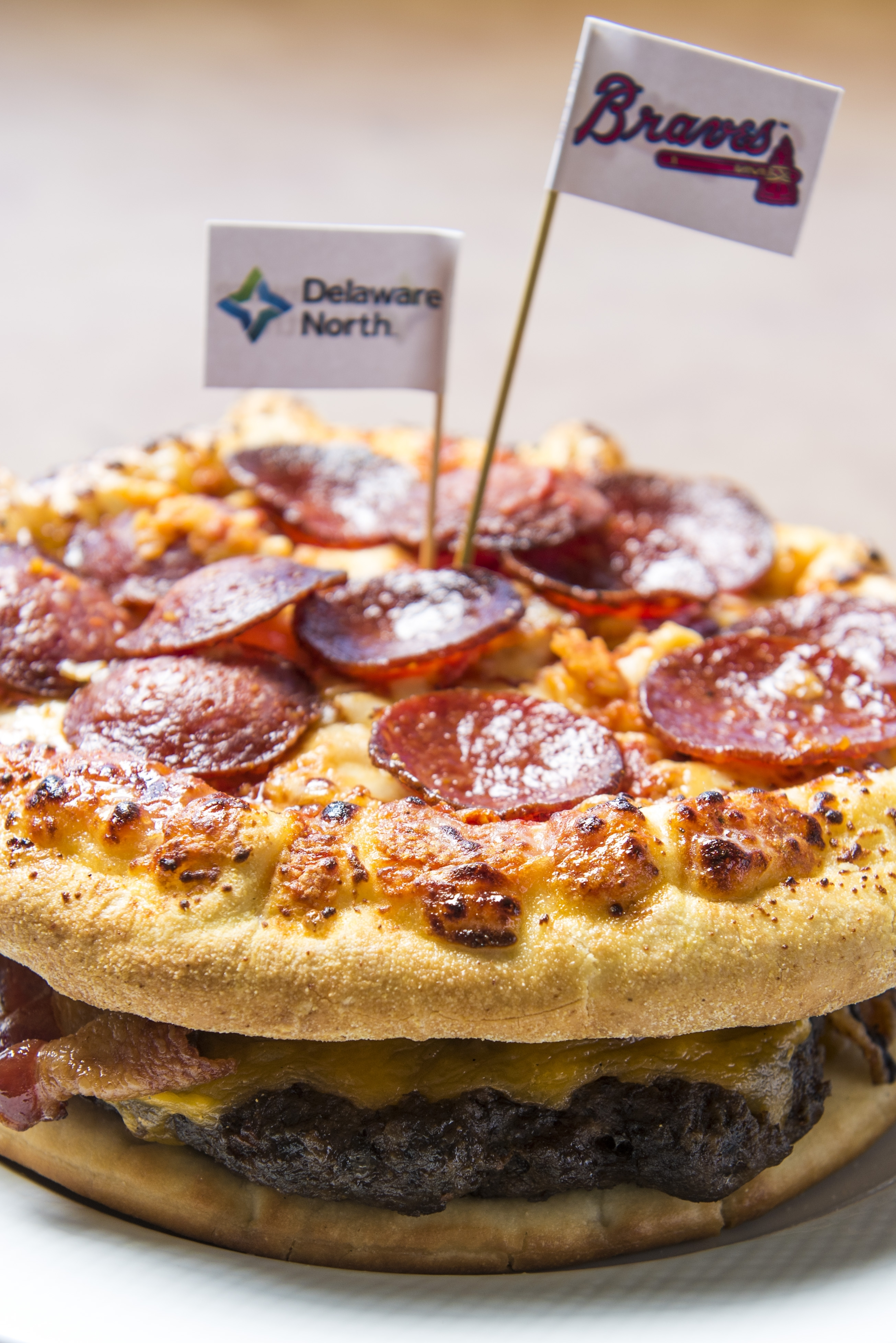 """In this March 22, 2016 photo released by the Atlanta Braves, the """"Burgerizza"""" is shown in Atlanta. A grilled 20oz. all beef patty, covered with five slices of cheddar cheese, topped with crispy bacon, and served between two 8-inch  Pepperoni Pizzas is one"""