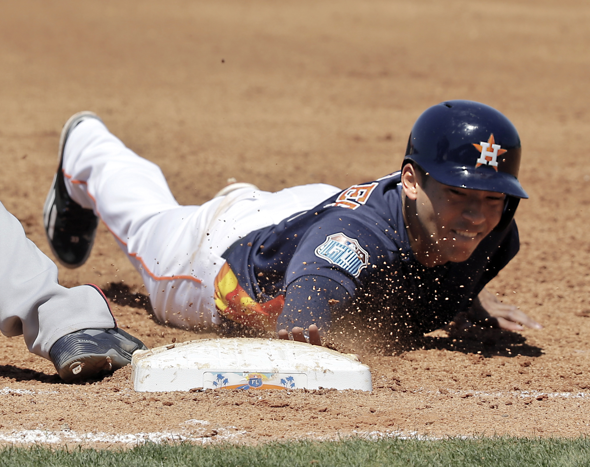Houston Astros' Carlos Correa dives safely back to first base in a pick off attempt by the Atlanta Braves during the fourth inning of a spring training baseball game, Tuesday, March 22, 2016, in Kissimmee, Fla. (AP Photo/John Raoux)