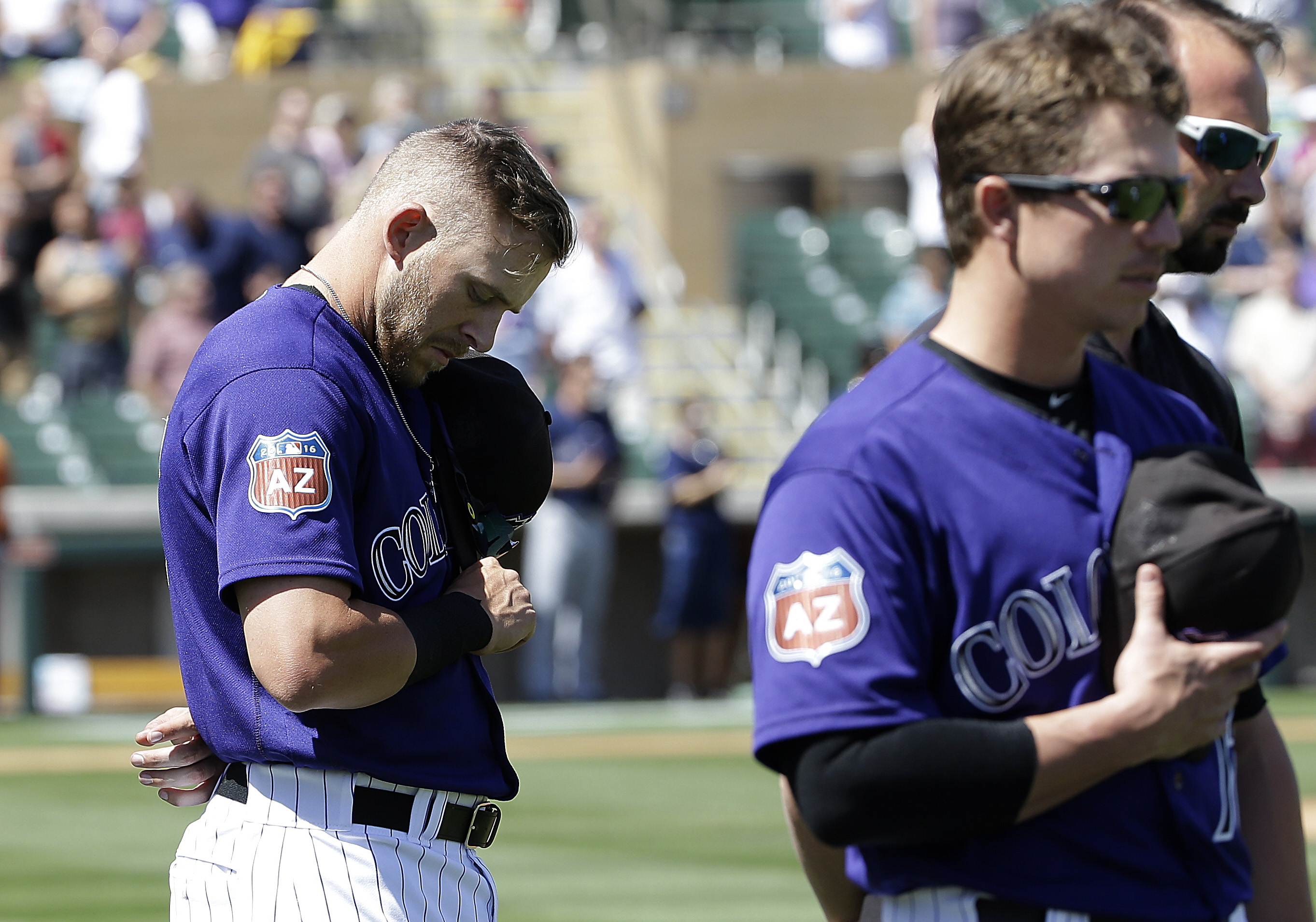 Colorado Rockies' Trevor Story, left, and Ryan Casteel observe a moment of silence for the victims of attacks in Brussels, Belgium, before a spring training baseball game between the Rockies and the Milwaukee Brewers in Scottsdale, Ariz., Tuesday, March 2