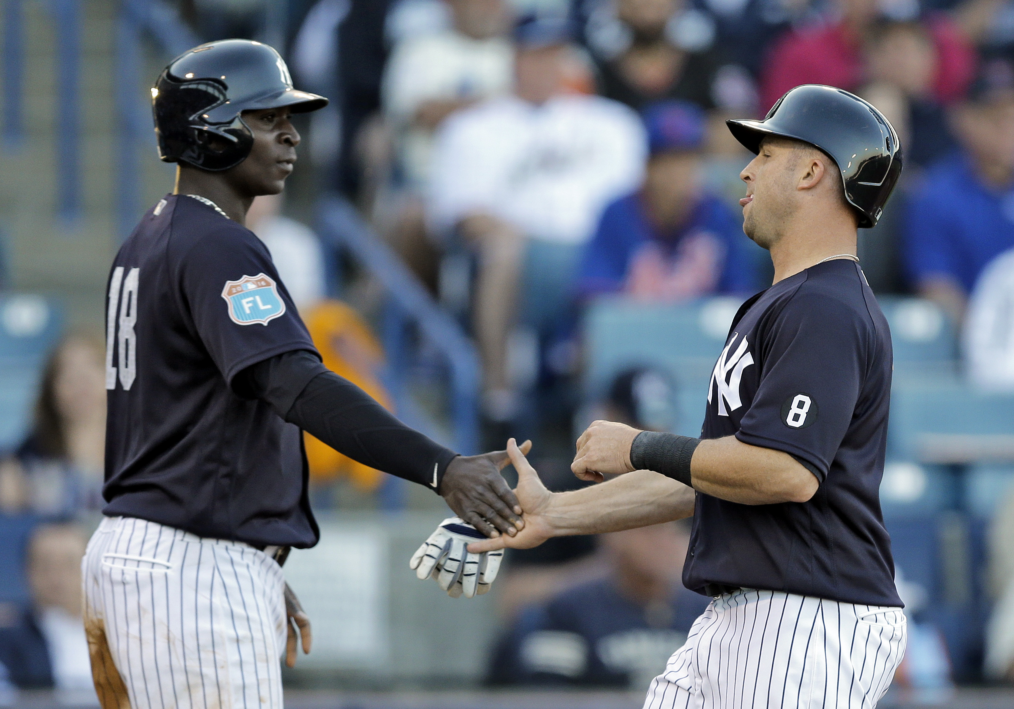 New York Yankees' Brett Gardner, right, and Didi Gregorius celebrate after scoring on a two-run single by Alex Rodriguez off New York Mets starting pitcher Steven Matz during the second inning of a spring training baseball game Tuesday, March 22, 2016, in