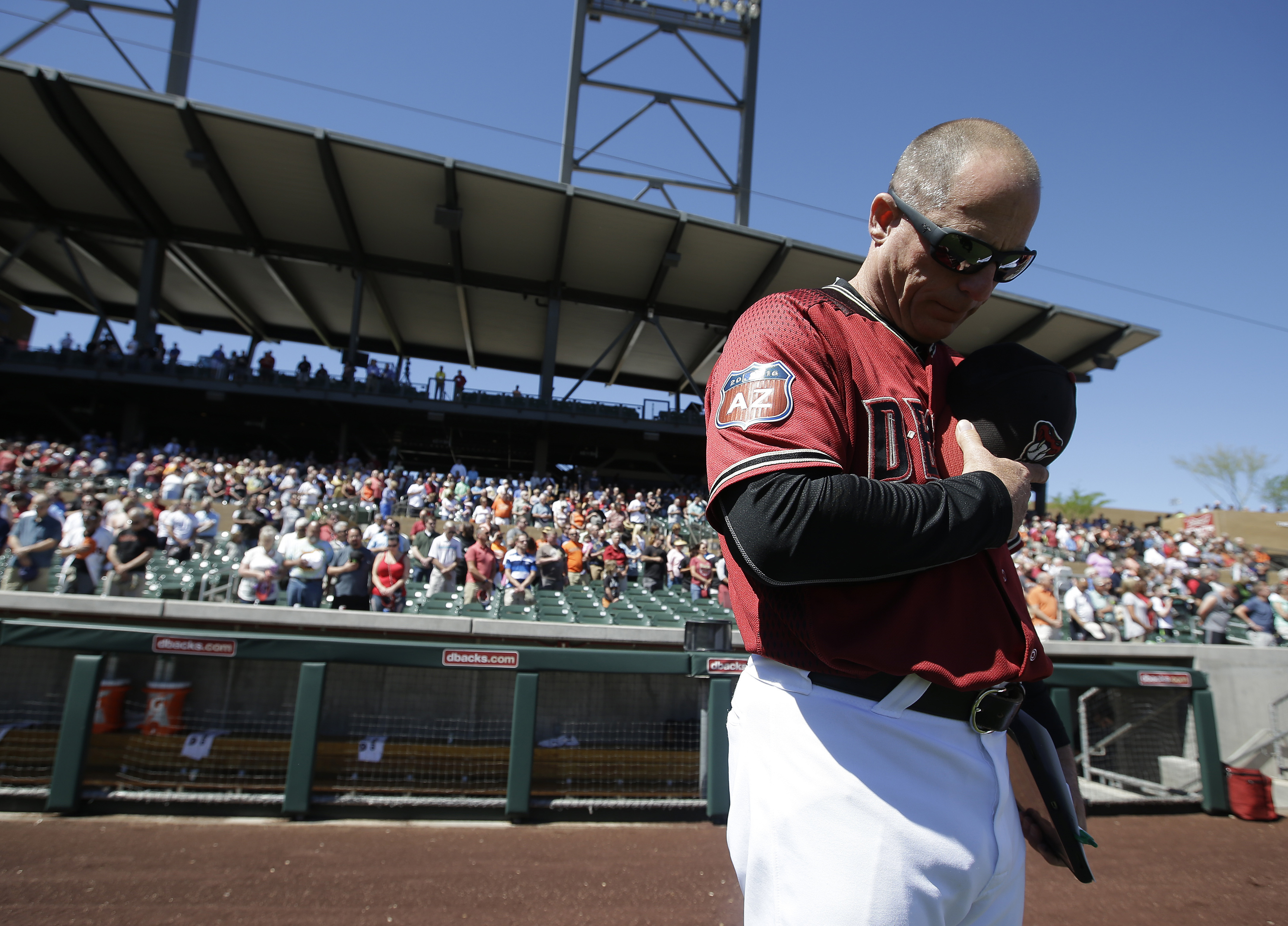 Arizona Diamondbacks manager Chip Hale bow his head during a moment of silence for Joe Garagiola before the team's spring training baseball game against the San Francisco Giants, Wednesday, March 23, 2016, in Scottsdale, Ariz. (AP Photo/Darron Cummings)
