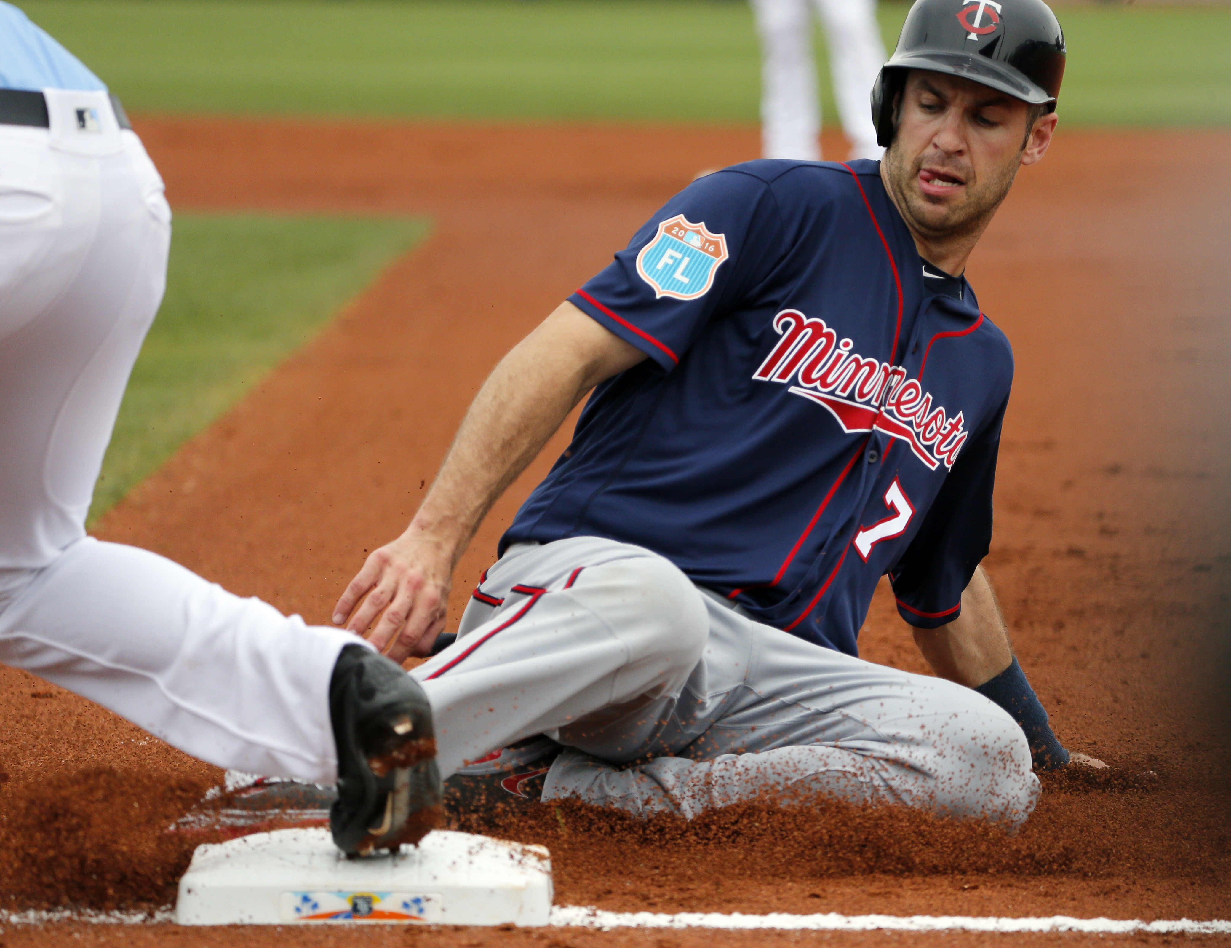 Minnesota Twins' Joe Mauer is forced out by Tampa Bay Rays' James Loney, left, trying to get back to first after Miguel Sano lined out to Tampa Bay Rays third baseman Evan Longoria in the first inning of a spring training baseball game, Friday, March 25,