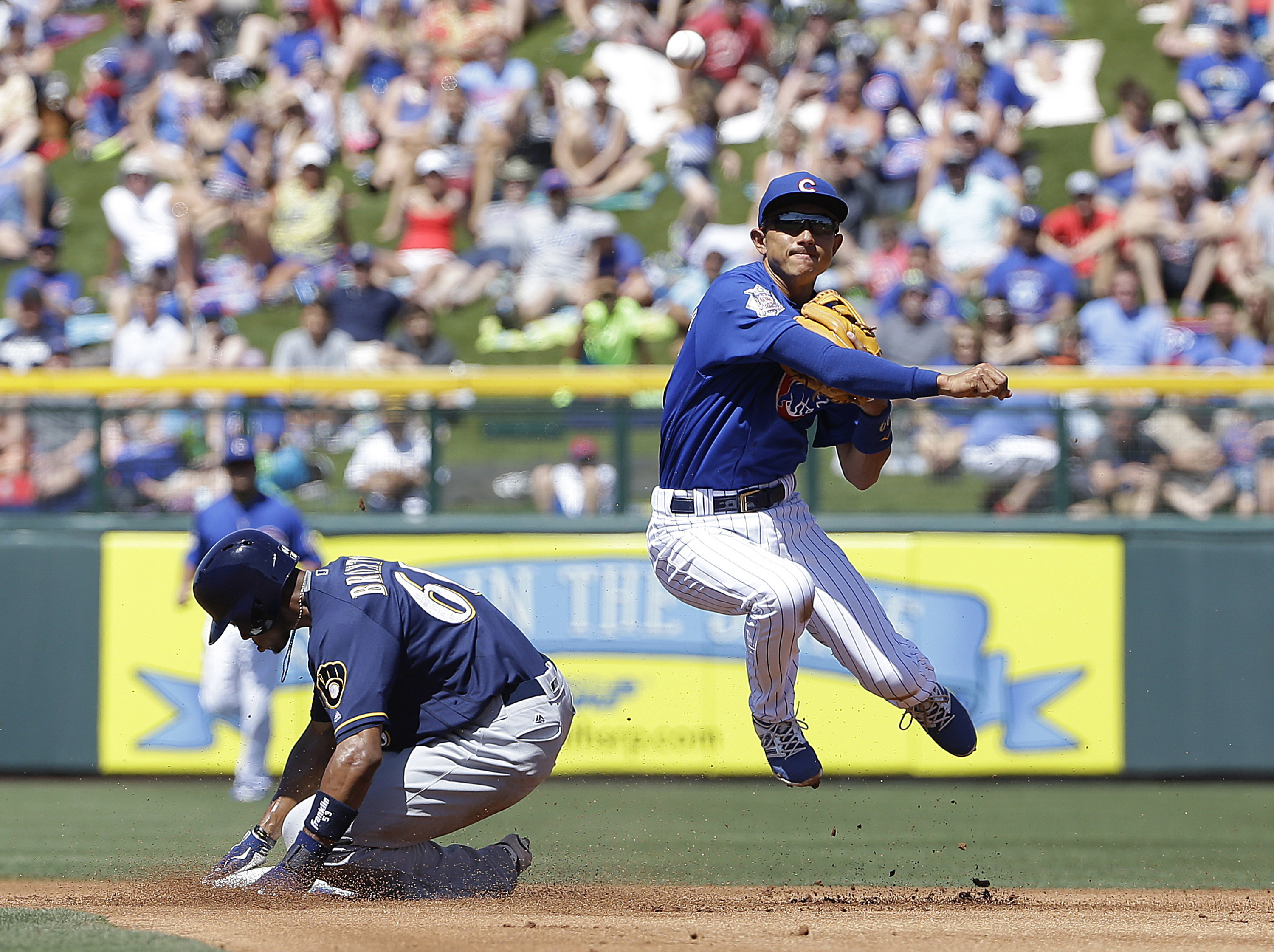 Chicago Cubs shortstop Munenori Kawasaki, right, throws to first base after forcing out Milwaukee Brewers' Keon Broxton at second base during the first inning of a spring training baseball game in Mesa, Ariz., Friday, March 25, 2016. (AP Photo/Jeff Chiu)