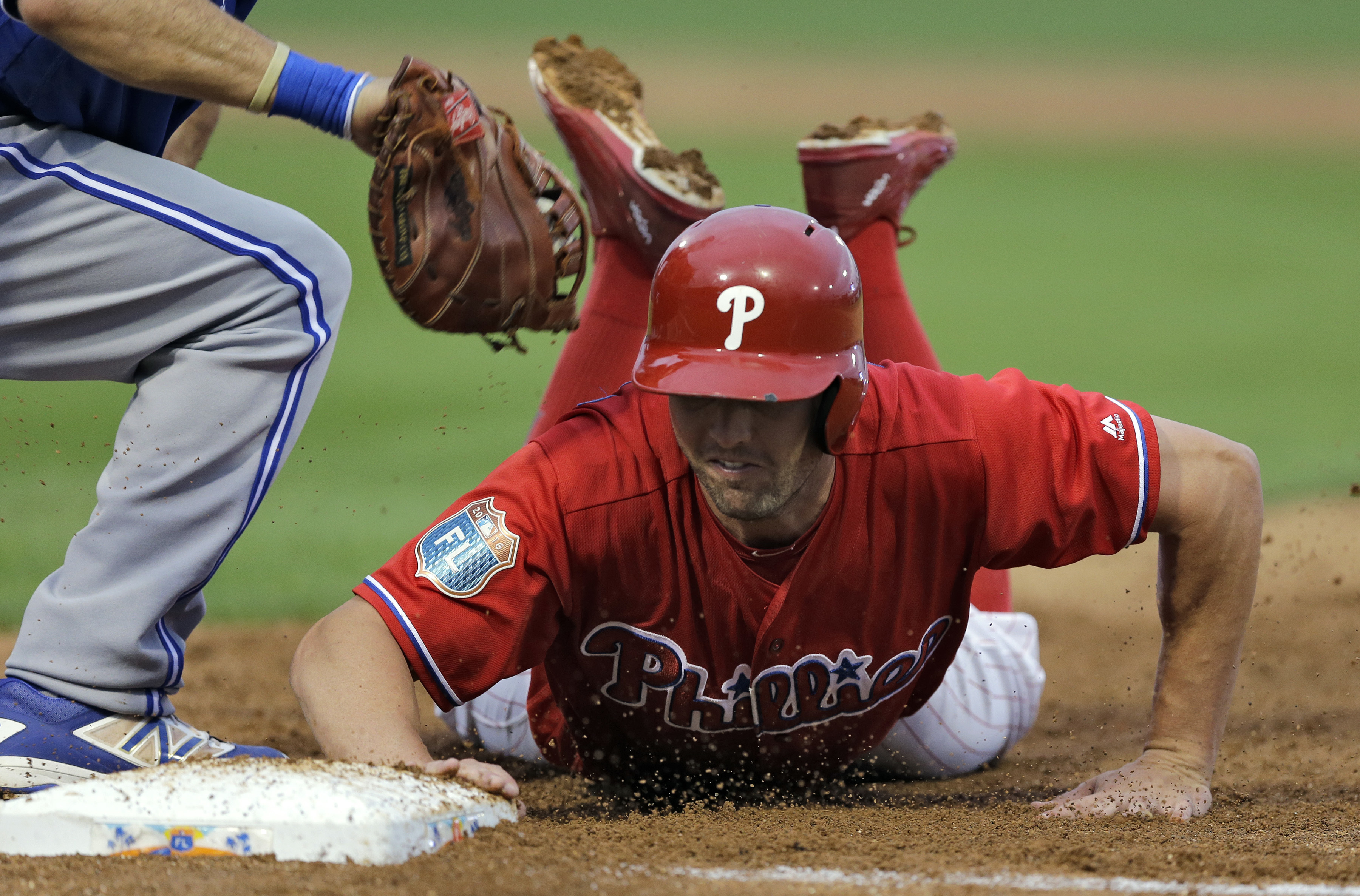 Philadelphia Phillies' Peter Bourjos dives back safely to first base ahead of the tag by Toronto Blue Jays' Casey Kotchman during the second inning of a spring training baseball game Friday, March 25, 2016, in Clearwater, Fla. (AP Photo/Chris O'Meara)