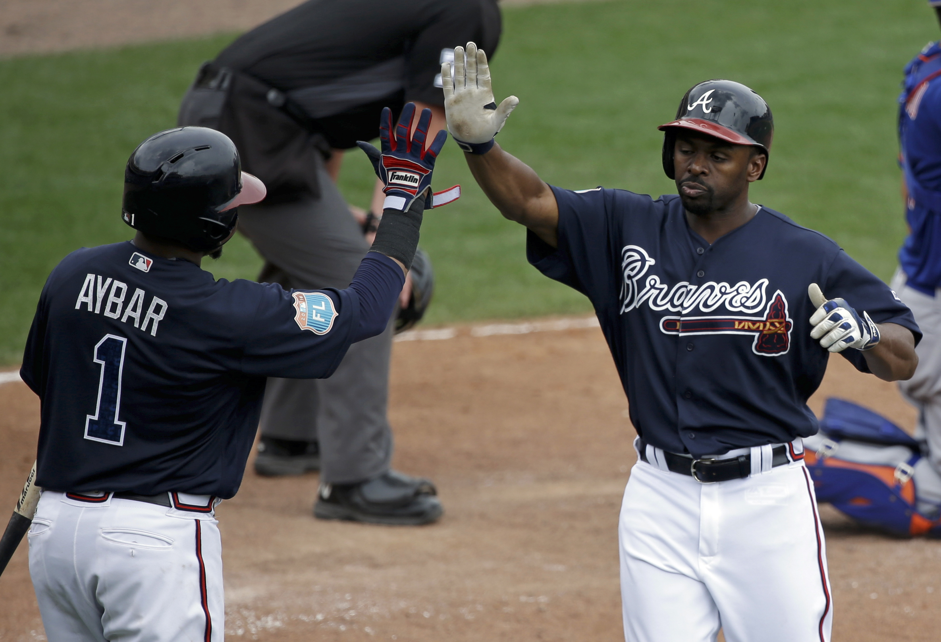 Atlanta Braves' Michael Bourn, right, gets a high-five from teammate Erick Aybar (1) after scoring a run in the sixth inning of a spring training baseball game against the New York Mets, Saturday, March 26, 2016, in Kissimmee, Fla. (AP Photo/John Raoux)