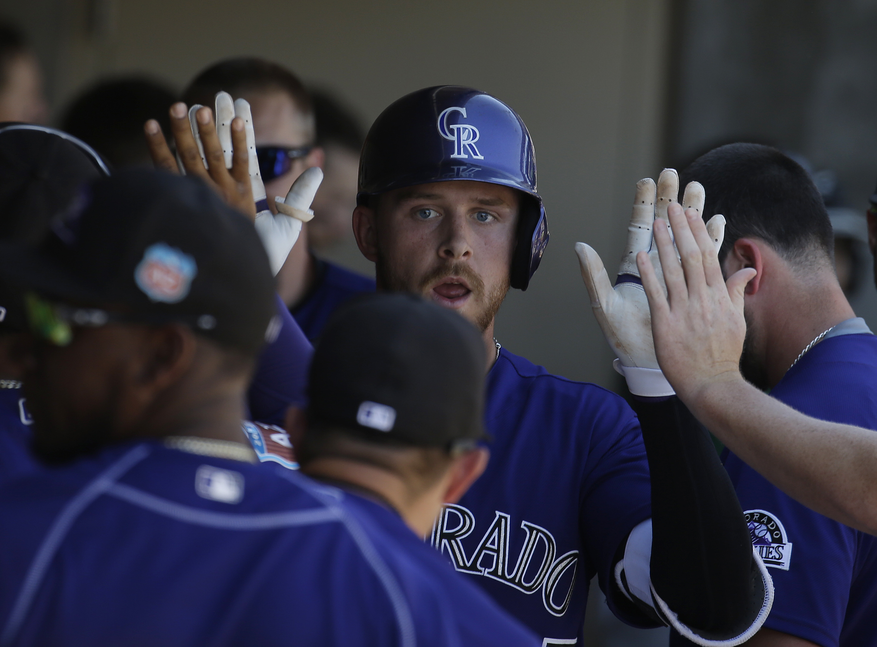 Colorado Rockies' Trevor Story celebrates with teammates after hitting a solo home run during the third inning of a spring training baseball game against the Texas Rangers, Saturday, March 26, 2016, in Scottsdale, Ariz. (AP Photo/Darron Cummings)