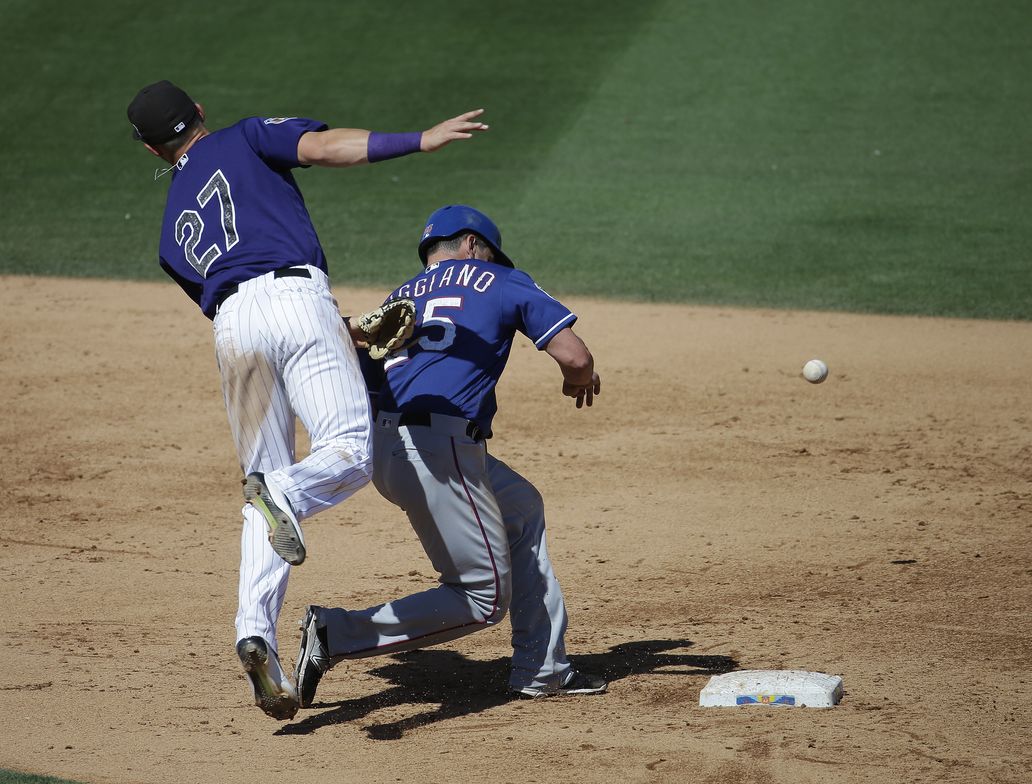 Colorado Rockies' Trevor Story (27) cannot catch a ball thrown by catcher Nick Hundley as Texas Rangers' Justin Ruggiano, right, runs back to second during the sixth inning of a spring training baseball game Saturday, March 26, 2016, in Scottsdale, Ariz.