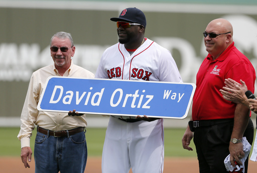 Lee County commissioners John Manning, left, and Cecil Pendegrass, right, present Boston Red Sox's David Ortiz with a street sign after city leaders honored Ortiz by renaming a street by the ballpark in his name during a ceremony before a spring training