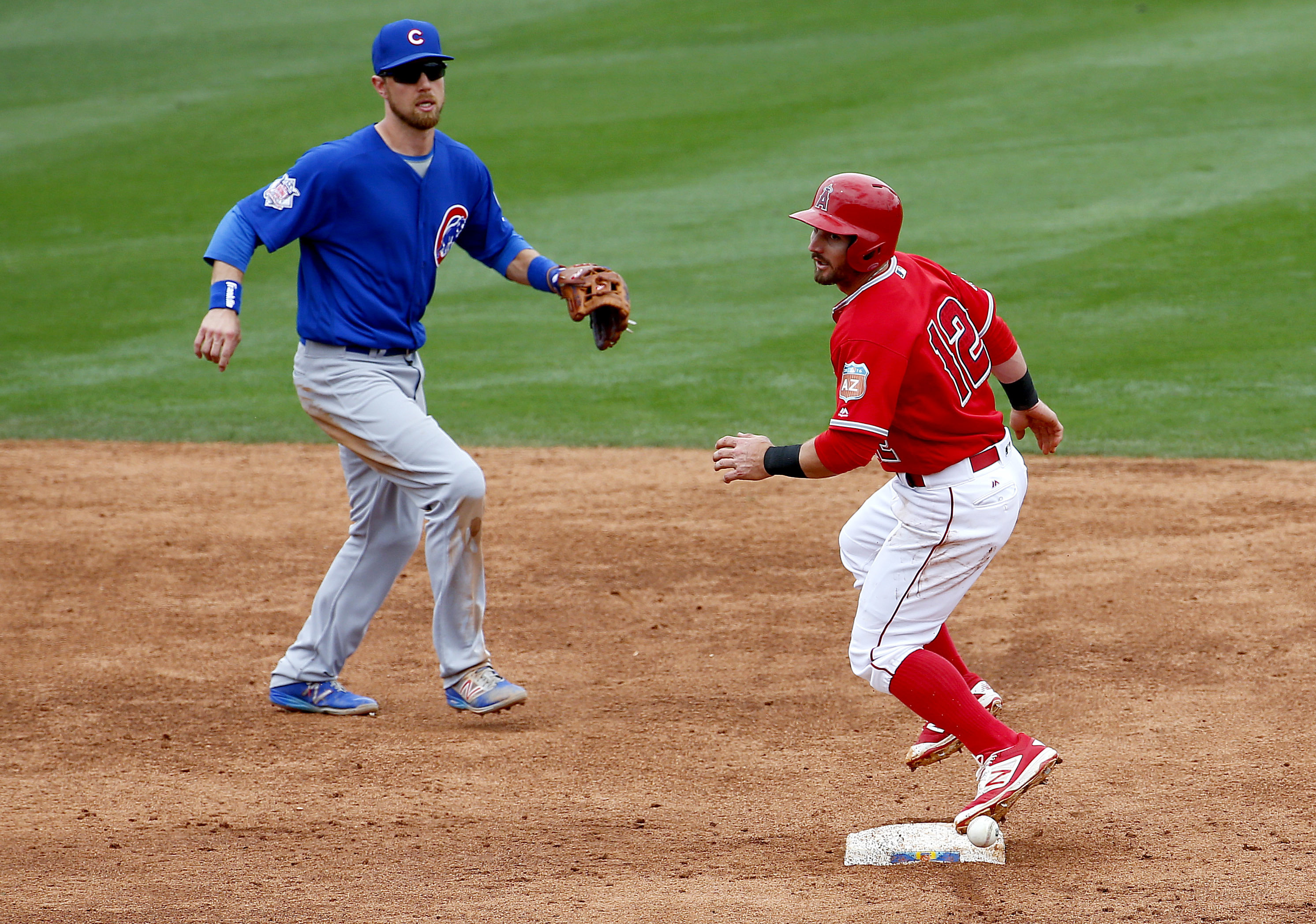 Los Angeles Angels' Johnny Giavotella (12) is out after running into a ground ball as Chicago Cubs' Ben Zobrist looks on during the third inning of a spring training baseball game, Monday, March 28, 2016, in Tempe, Ariz. (AP Photo/Matt York)
