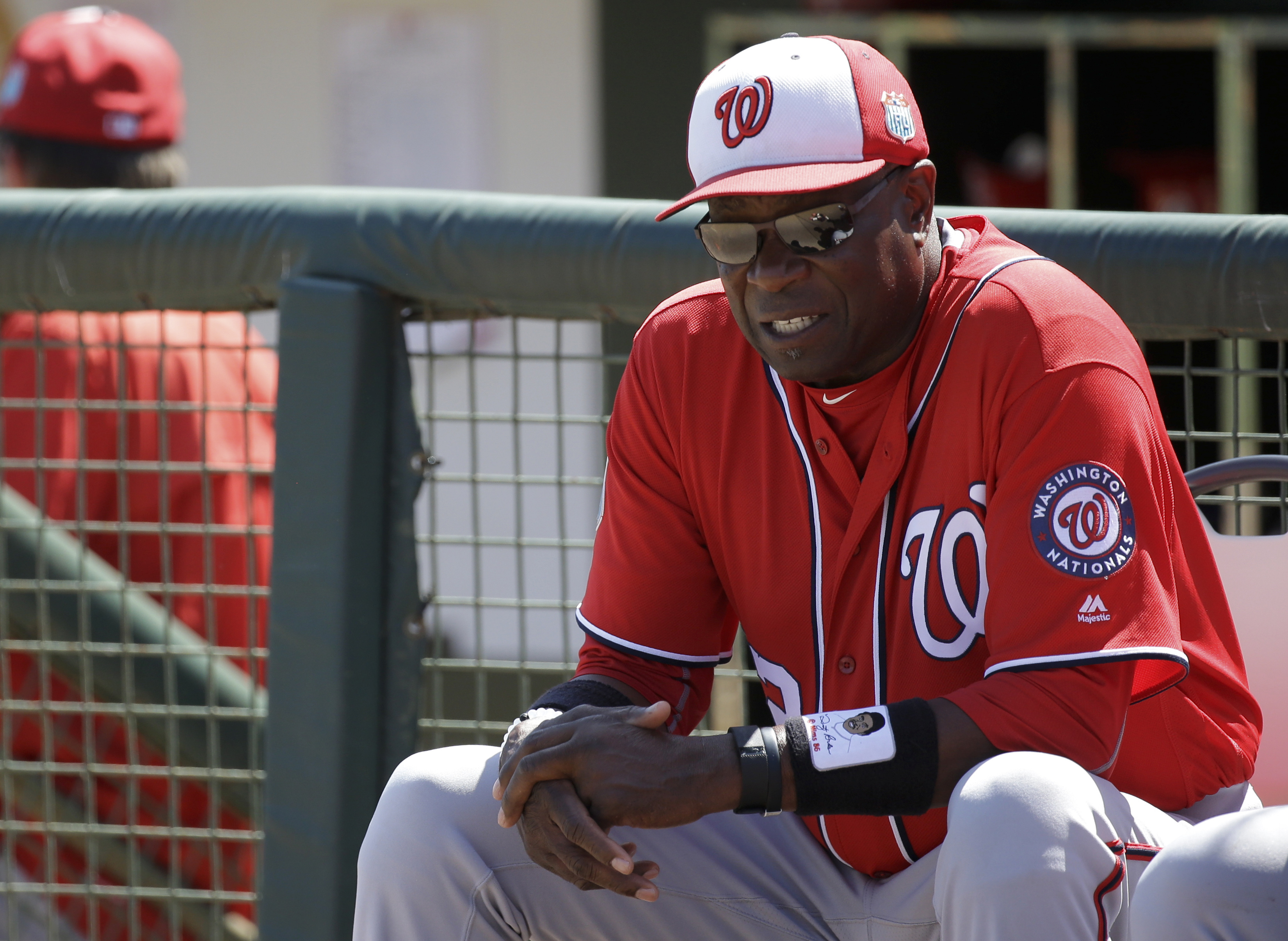 FILE - In this March 15, 2016, file photo, Washington Nationals manager Dusty Baker sits outside the dugout during a spring training baseball game against the Houston Astros, in Kissimmee, Fla. When managing the Cincinnati Reds, Dusty Baker always had a d