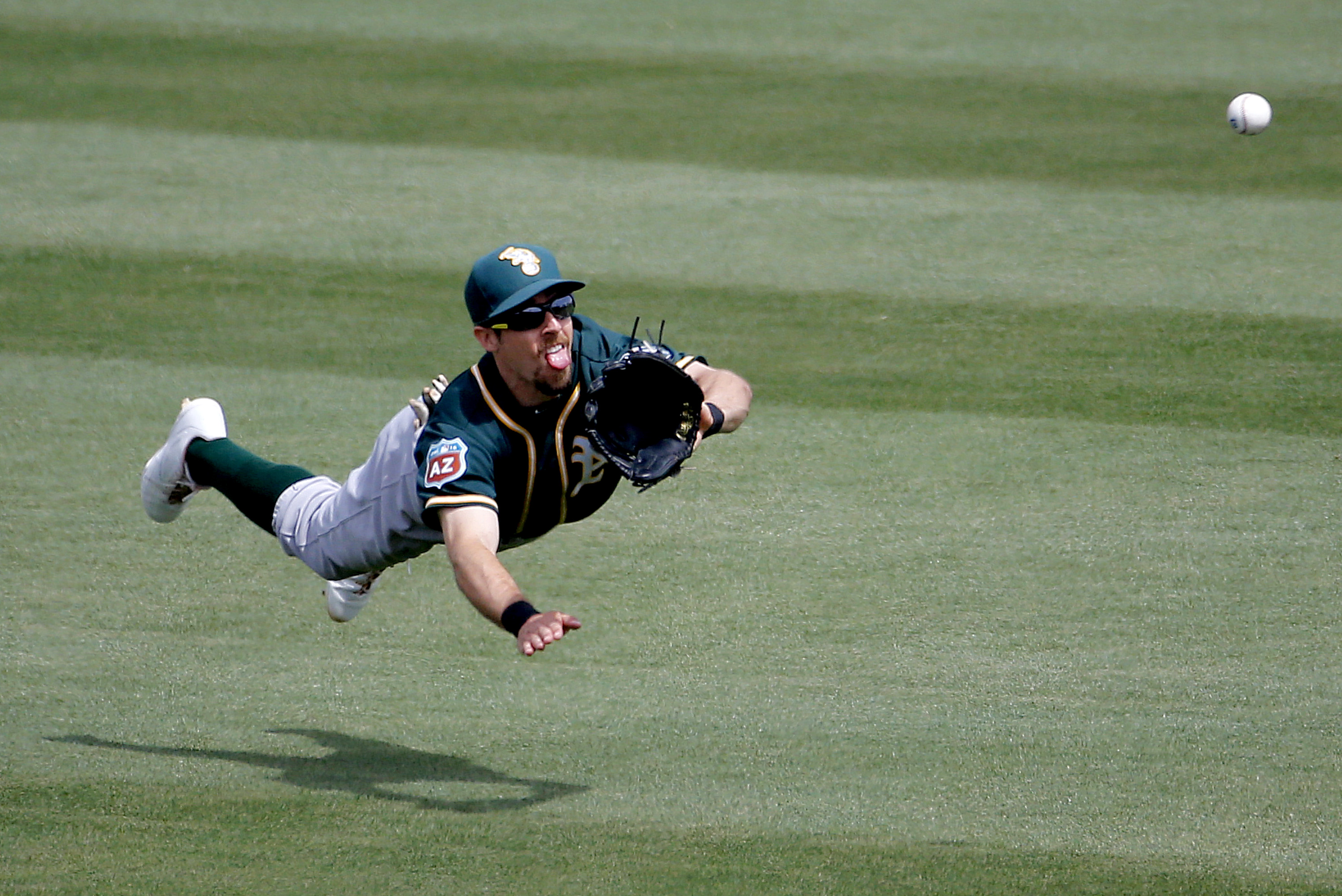 Oakland Athletics BIlly Burns can't make the catch on a base hit by Chicago Cubs' Miguel Montero during the second inning of a spring training baseball game, Tuesday, March 29, 2016, in Mesa, Ariz. (AP Photo/Matt York)