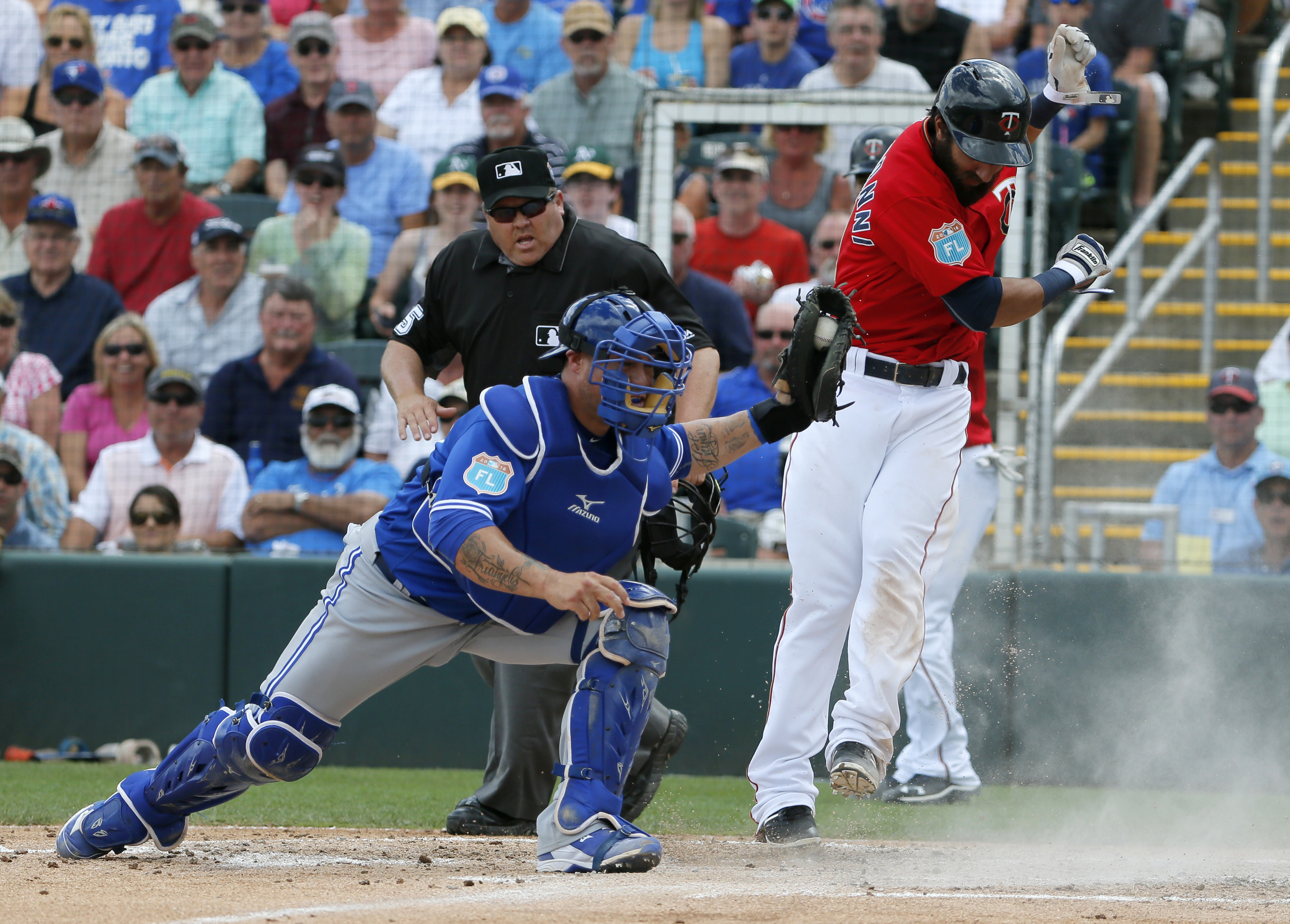 Minnesota Twins' Darin Mastroianni avoids a tag attempt by Toronto Blue Jays' Humberto Quintero as umpire Fieldin Culbreth watches in the second inning of a spring training baseball game, Wednesday, March 30, 2016, in Fort Myers, Fla. Mastroianni and Kurt