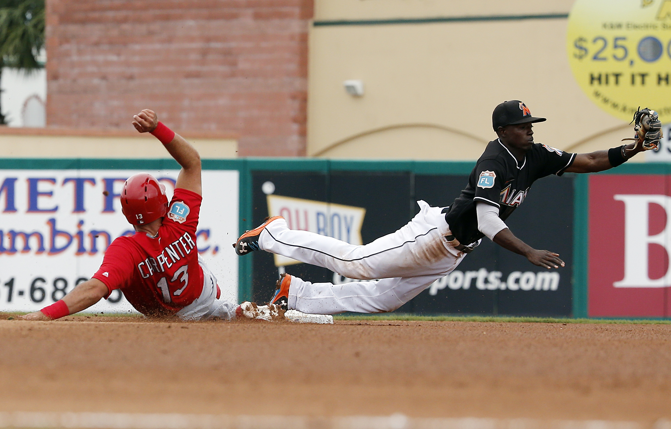 St. Louis Cardinals' Matt Carpenter slides safely into second base after Miami Marlins second baseman Dee Gordon misses the ball during the fourth inning of an exhibition spring training baseball game, Wednesday, March 30, 2016, in Jupiter, Fla. (AP Photo