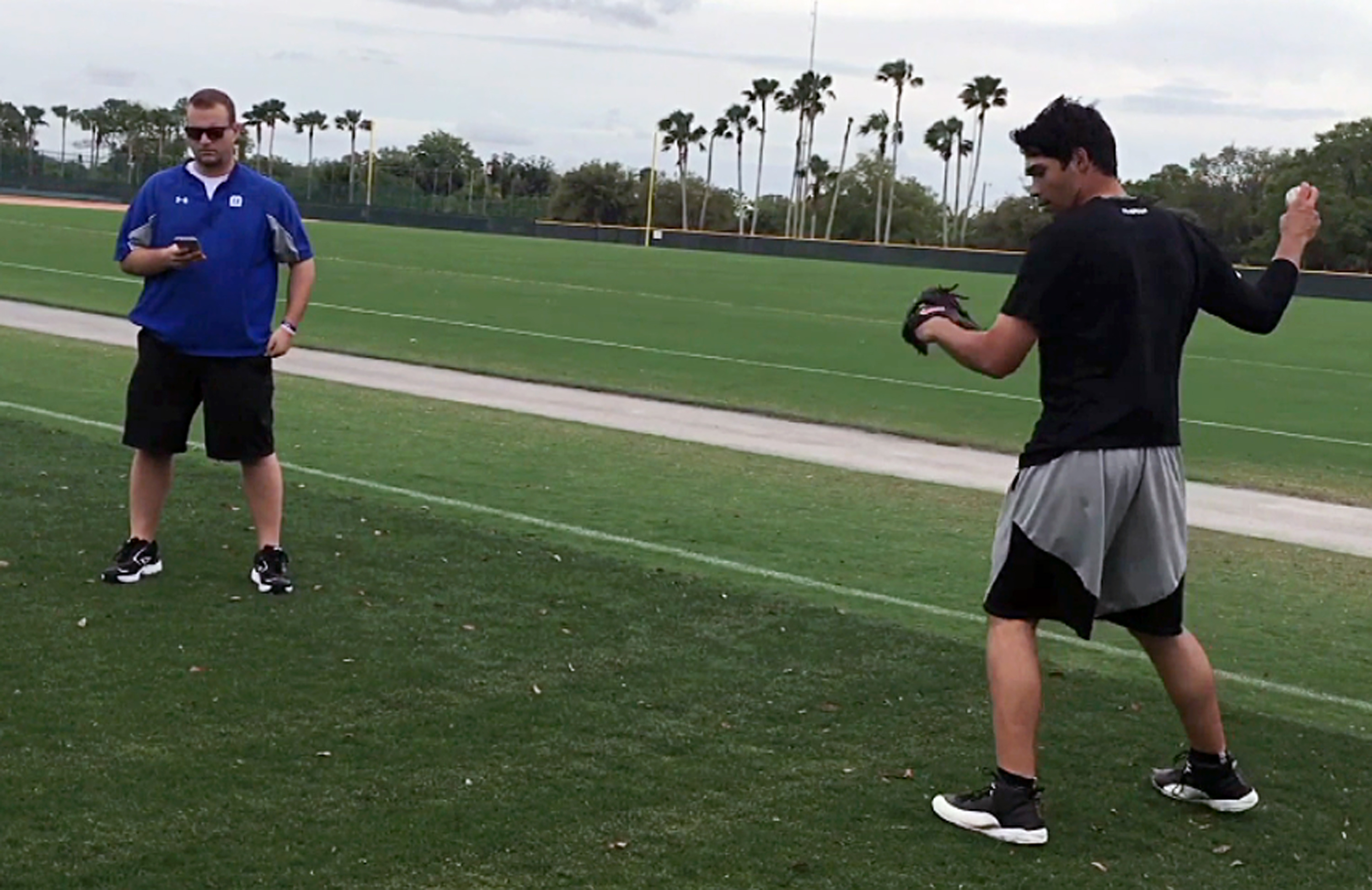 In this photo taken Sunday, March 20, 2016, Ben Hansen, chief technology officer of Motus Global, left, watches data on a hand held device as Pittsburgh Pirates prospect Matt Benedict throws at the Pirates minor league complex in Bradenton, Fla. Benedict