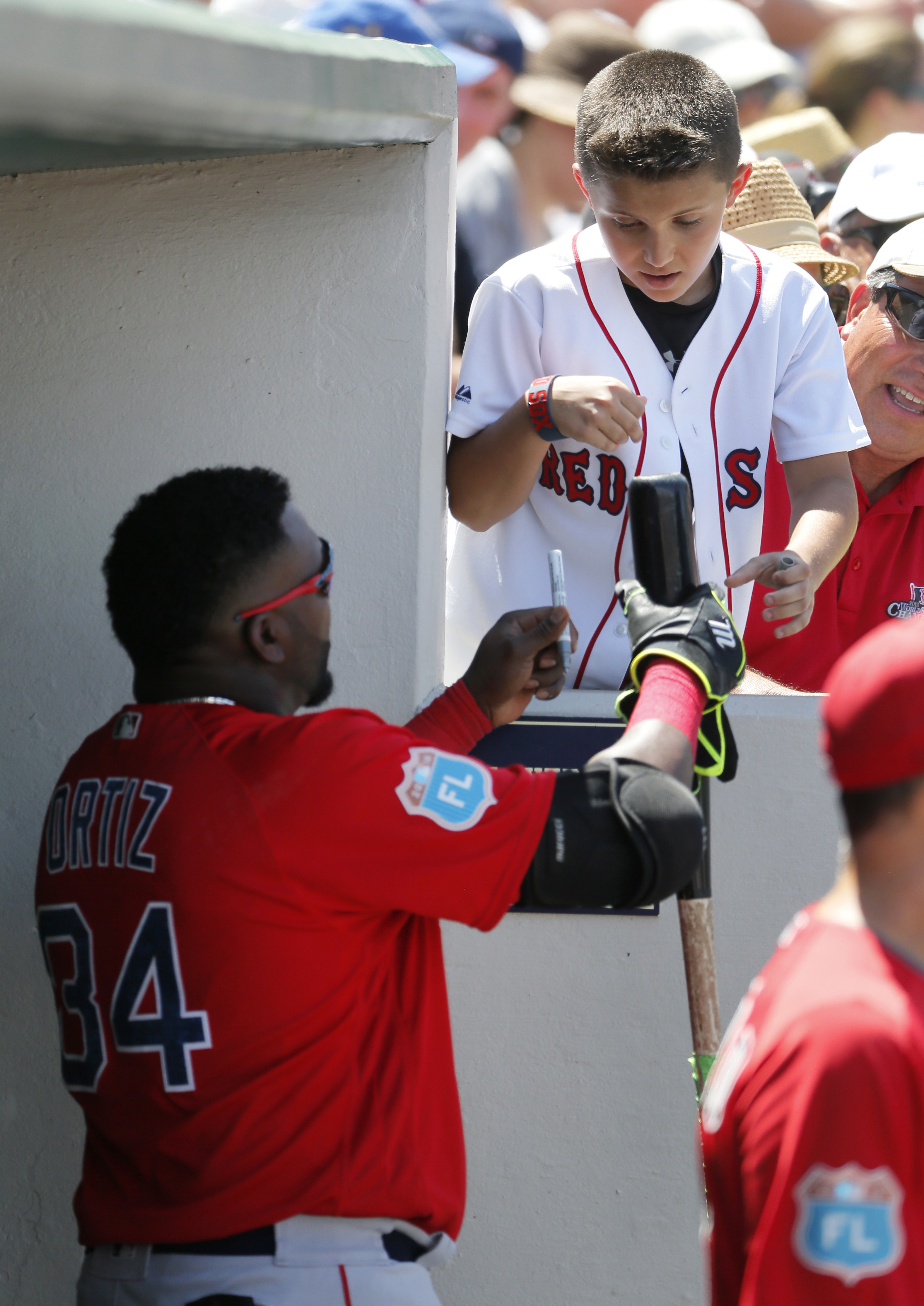Boston Red Sox's David Ortiz (34) hands a bat to a young fan after autographing it before going out for his at-bat in the fifth inning of a spring training baseball game against the Boston Red Sox on Thursday, March 31, 2016, in Fort Myers, Fla. (AP Photo