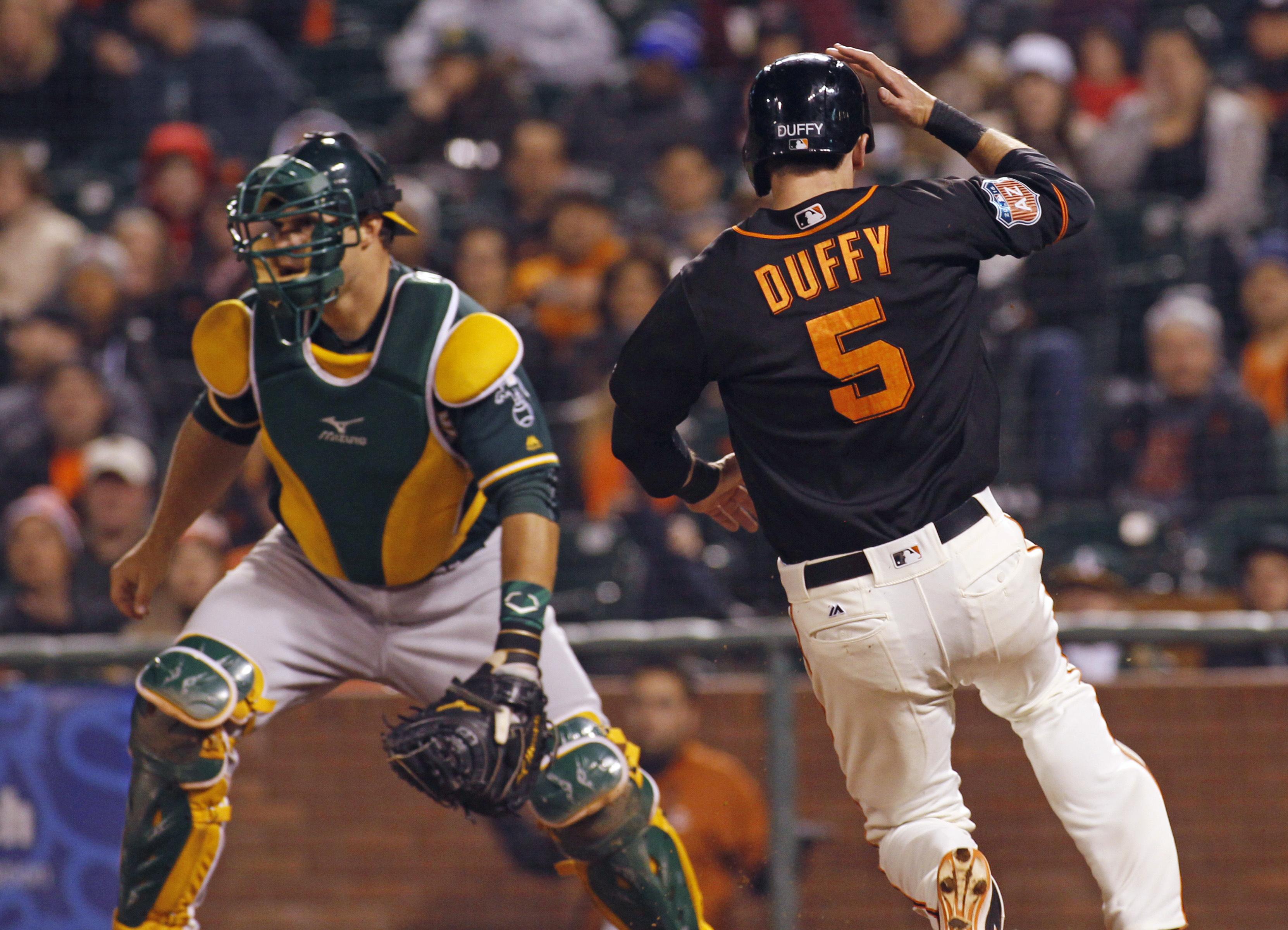 San Francisco Giants' Matt Duffy scores on a Gregor Blanco single as Oakland Athletics' Josh Phegley awaits a throw during the seventh inning of an exhibition baseball game, Friday, April 1, 2016, in San Francisco. (AP Photo/George Nikitin)