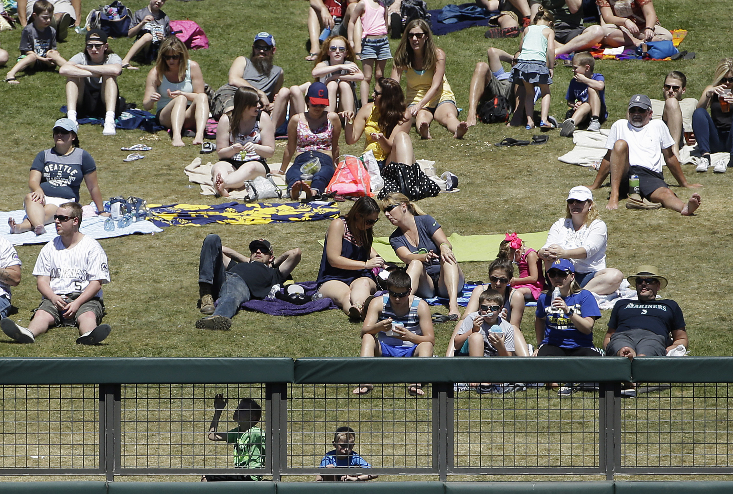 Fans watch from the outfield lawn during the third inning of a spring training baseball game between the Colorado Rockies and the Seattle Mariners in Scottsdale, Ariz., Saturday, April 2, 2016. (AP Photo/Jeff Chiu)