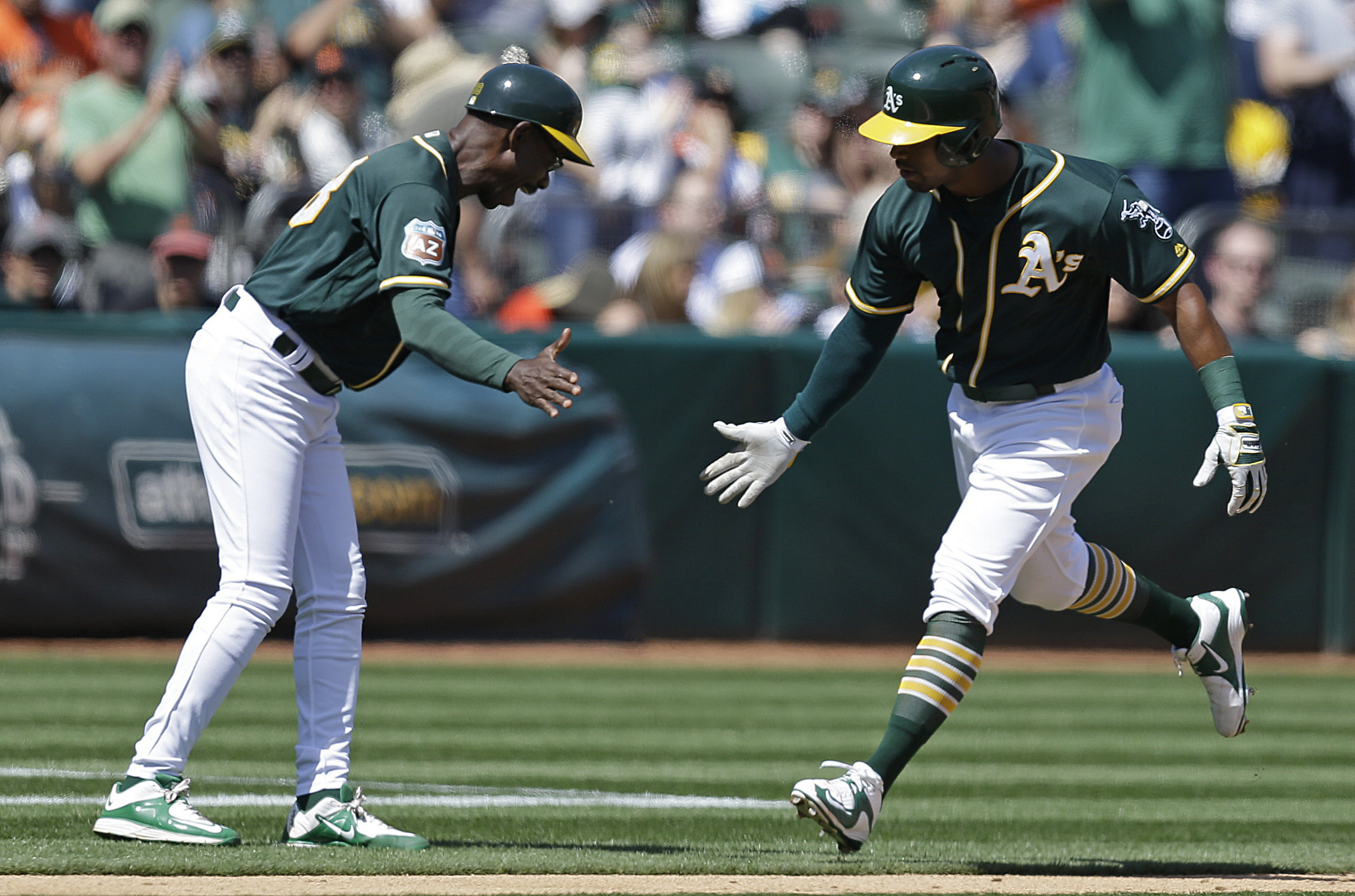 Oakland Athletics' Khris Davis, right, celebrates with third base coach Ron Washington after hitting a home run off San Francisco Giants' Matt Cain in the third inning of an exhibition baseball game Saturday, April 2, 2016, in Oakland, Calif. (AP Photo/Be