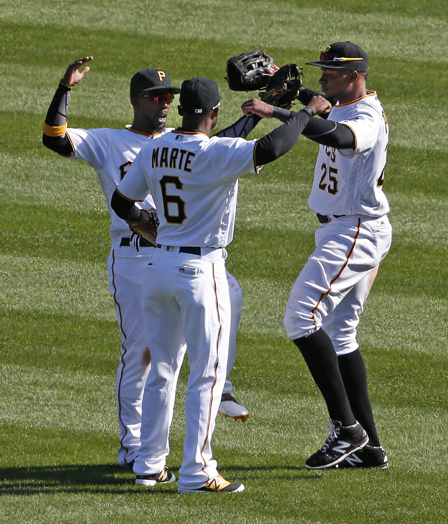 Pittsburgh Pirates outfielders Andrew McCutchen, left, Starling Marte (6) and Gregory Polanco (25) celebrate a 4-1 Major League Baseball opening day win over the St. Louis Cardinals in Pittsburgh, Sunday, April 3, 2016. (AP Photo/Gene J. Puskar)