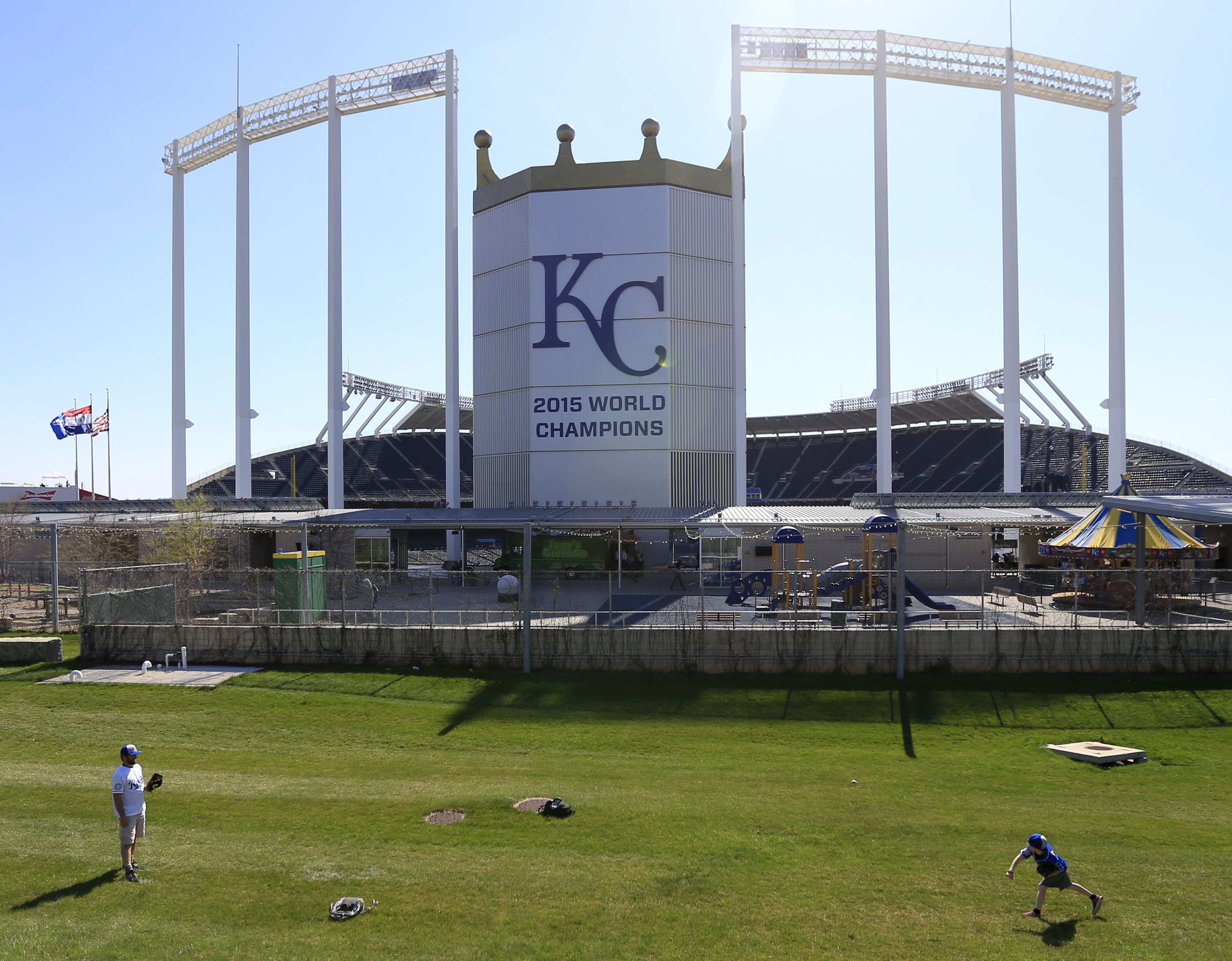 Jason, left, and Joshua Neland play catch behind the scoreboard at Kauffman Stadium before a Major League Baseball opening day game between the Kansas City Royals and the New York Mets in Kansas City, Mo., Sunday, April 3, 2016. (AP Photo/Orlin Wagner)