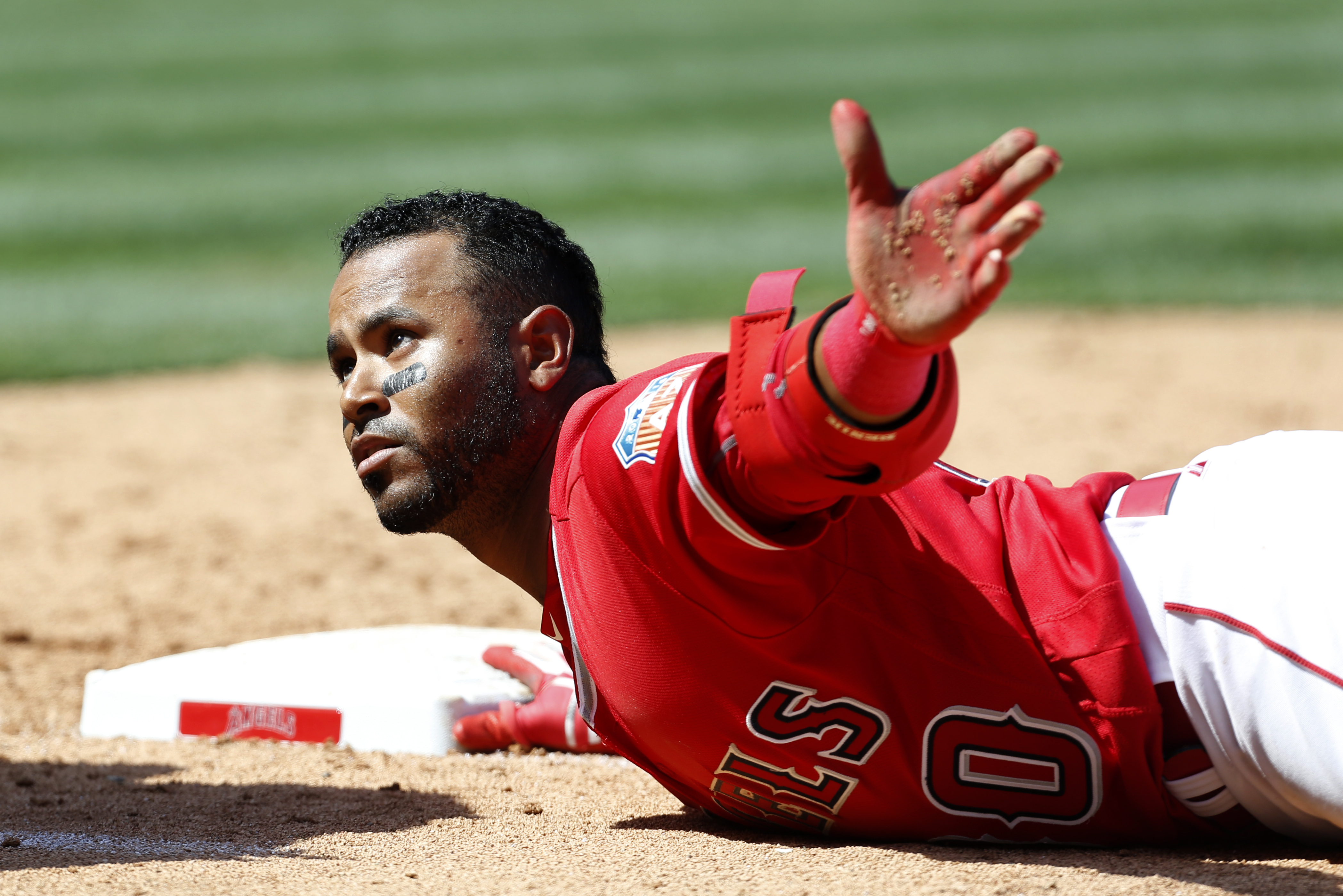 Los Angeles Angels' Gregorio Petit dives back to first base after hitting an RBI-single in the eighth inning against the Chicago Cubs in a spring exhibition baseball game in Anaheim, Calif., Sunday, April 3, 2016. (AP Photo/Christine Cotter)