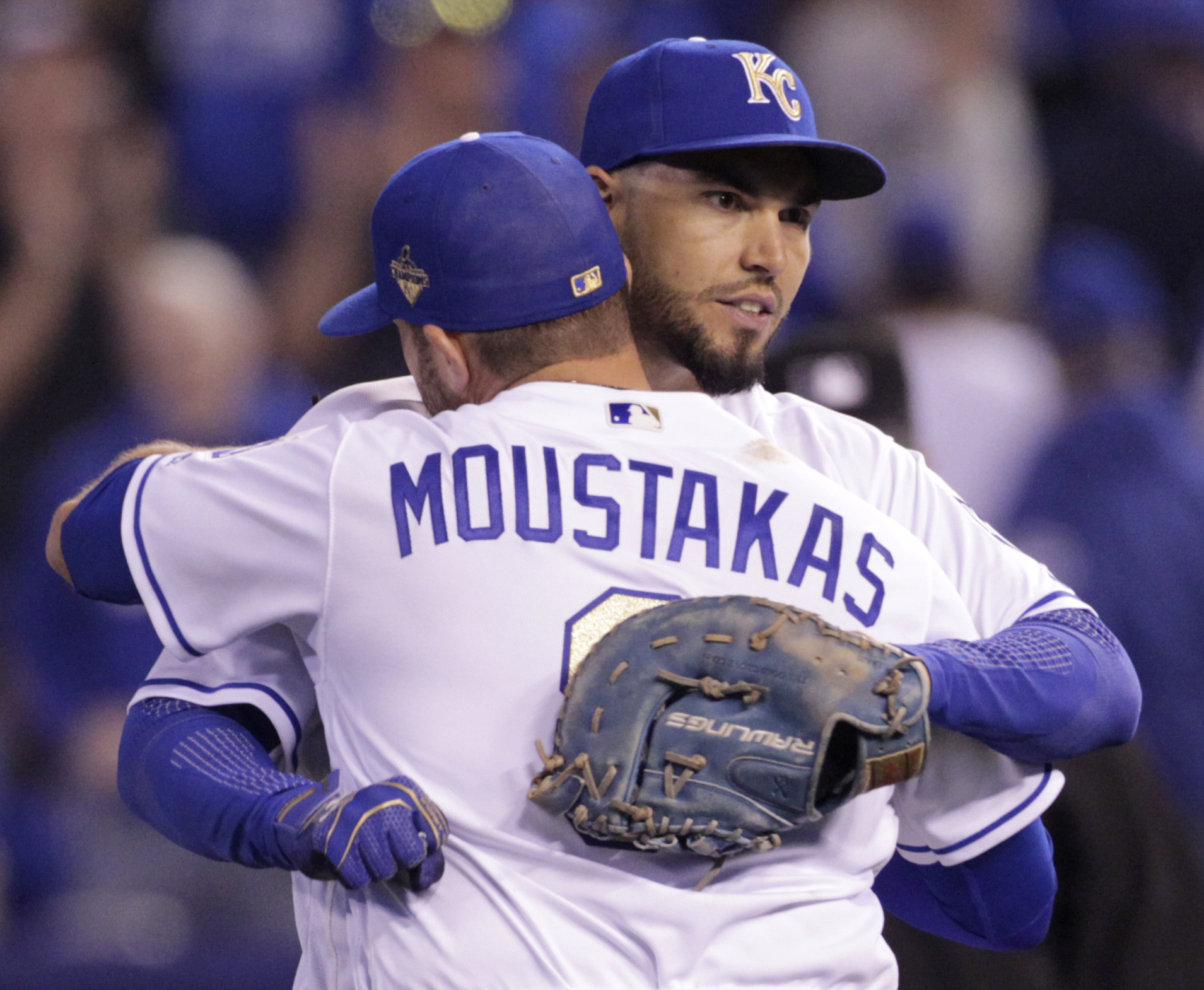 Kansas City Royals first baseman Eric Hosmer, background, celebrates with teammate Mike Moustakas (8) following a baseball game against the New York Mets at Kauffman Stadium in Kansas City, Mo., Sunday, April 3, 2016. The Royals defeated the Mets 4-3. (AP