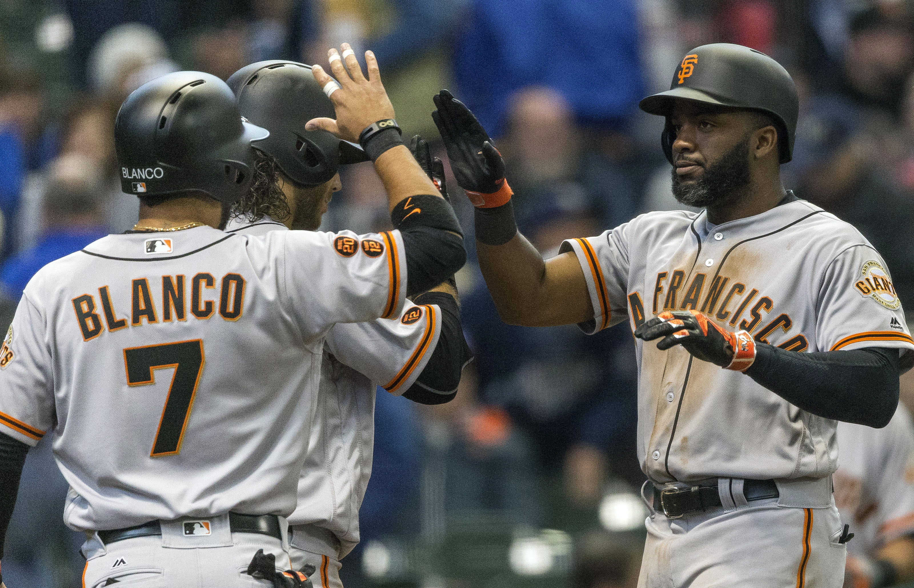 San Francisco Giants' Denard Span, right, is created by teammates Gregor Blanco and Brandon Crawford after hitting a three-run home run off Milwaukee Brewers' Ariel Pena during the eighth inning of a baseball game Monday, April 4, 2016, in Milwaukee. (AP
