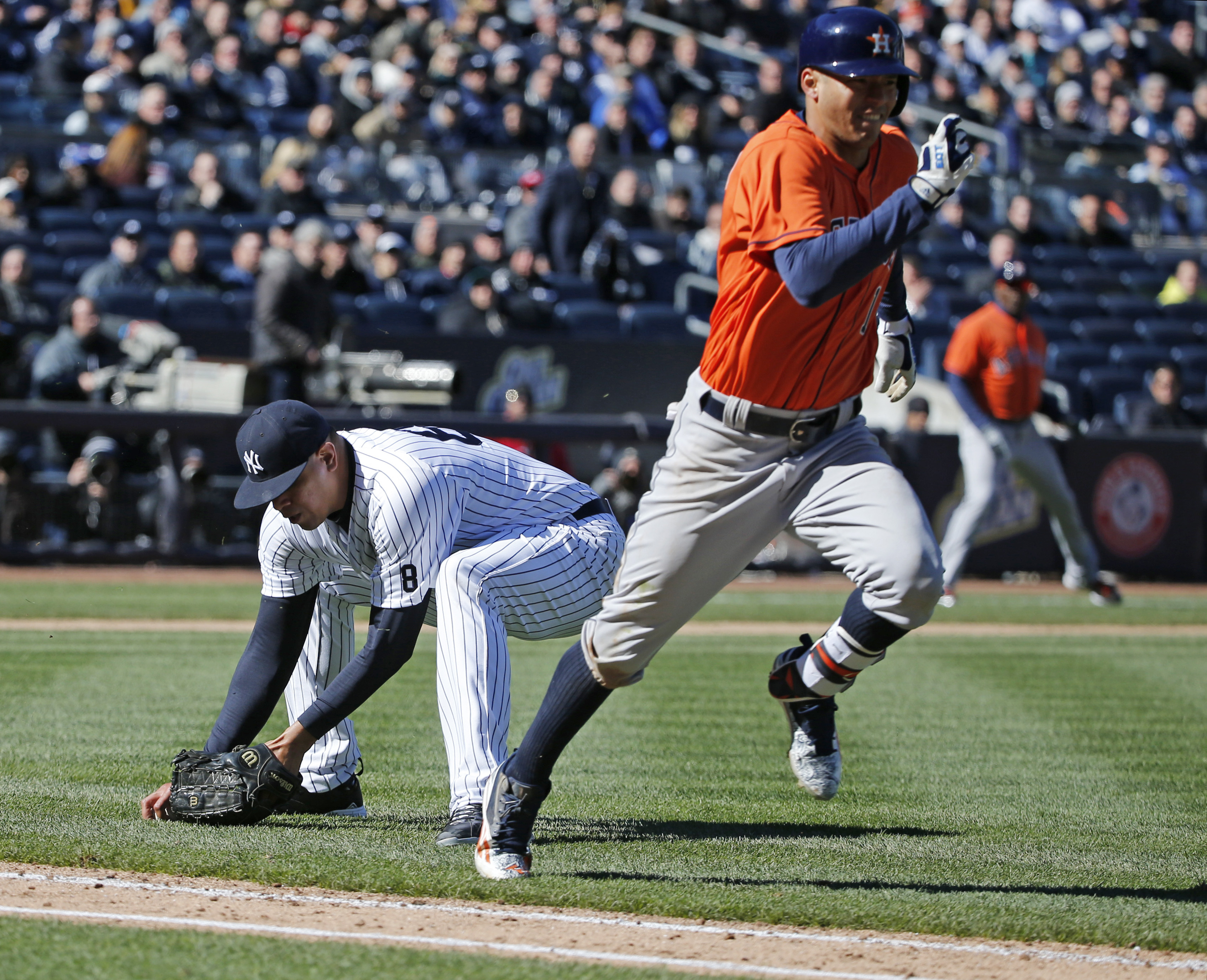 New York Yankees relief pitcher Dellin Betances (68) picks up Carlos Correa's eighth-inning infield roller as Correa races to first base in an opening day baseball game in New York, Tuesday, April 5, 2016. Correa reached on a Betances throwing error, but