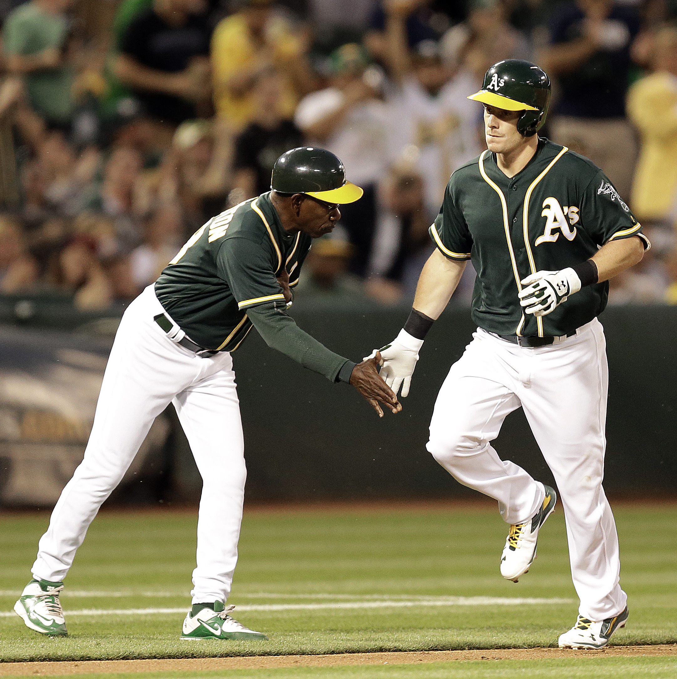 Oakland Athletics' Mark Canha, right, is congratulated by third base coach Ron Washington after hitting a home run off Chicago White Sox pitcher Carlos Rodon during the second inning of a baseball game Wednesday, April 6, 2016, in Oakland, Calif. (AP Phot