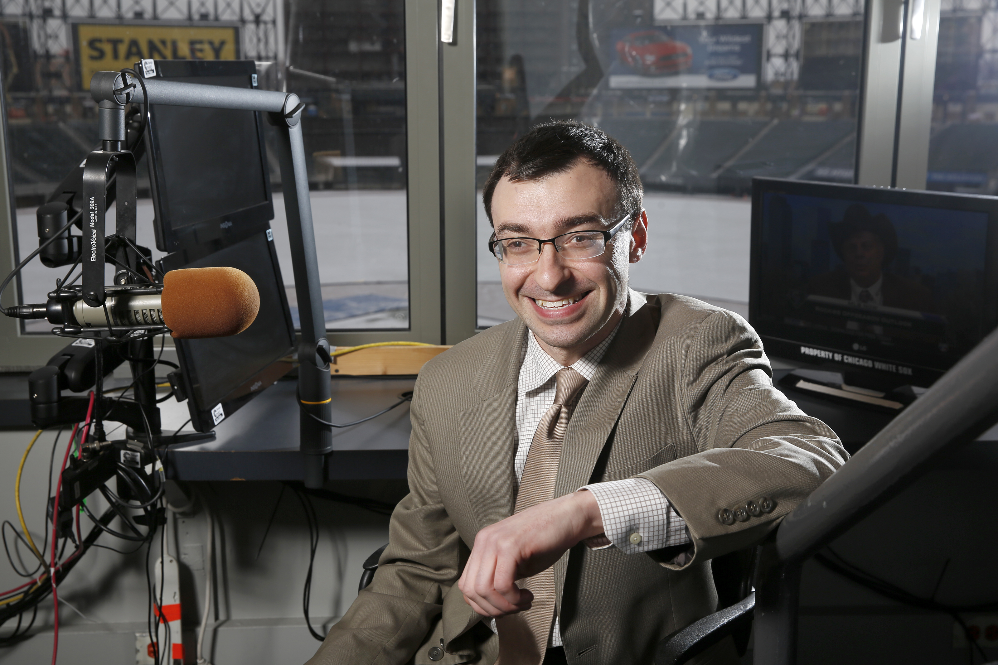 In this Monday Jan. 11, 2016 photo, New White Sox announcer Jason Benetti poses in his chair at U.S. Cellular Field in Chicago. In just a decade, Jason Benetti has gone from intense student at Syracuse University to the television broadcast booth calling