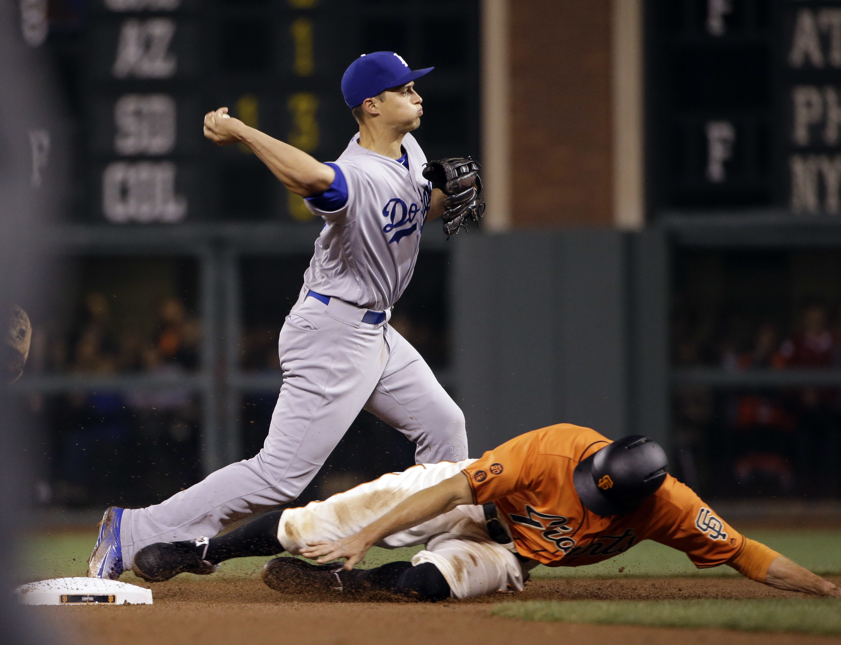Los Angeles Dodgers shortstop Corey Seager throws to first after forcing out San Francisco Giants' Hunter Pence at second base on a ground ball by Brandon Belt during the seventh inning of a baseball game Friday, April 8, 2016, in San Francisco. Belt was