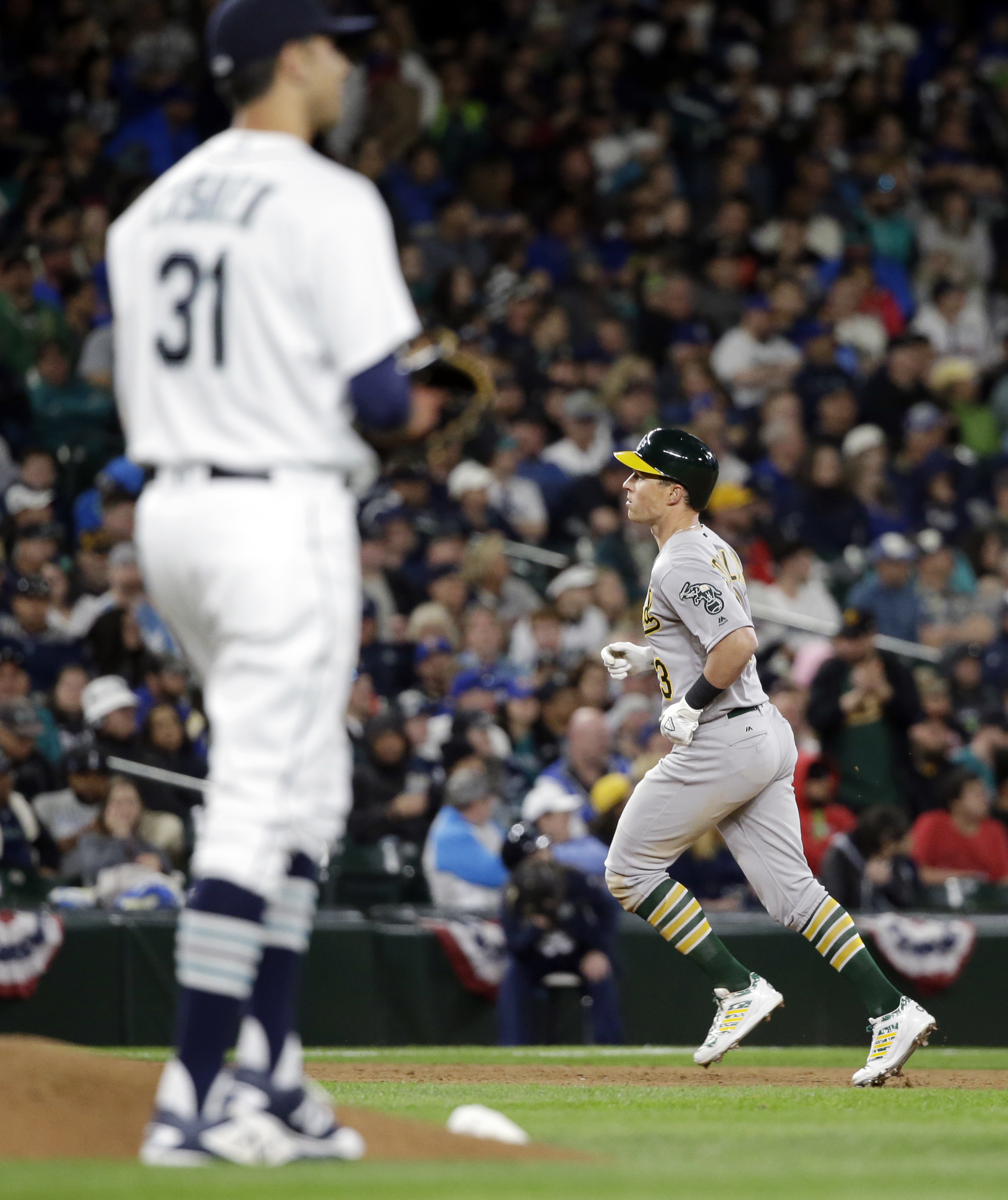 Seattle Mariners relief pitcher Steve Cishek waits as Oakland Athletics' Chris Coghlan rounds the bases on his home run during the ninth inning of a baseball game Friday, April 8, 2016, in Seattle. (AP Photo/Elaine Thompson)