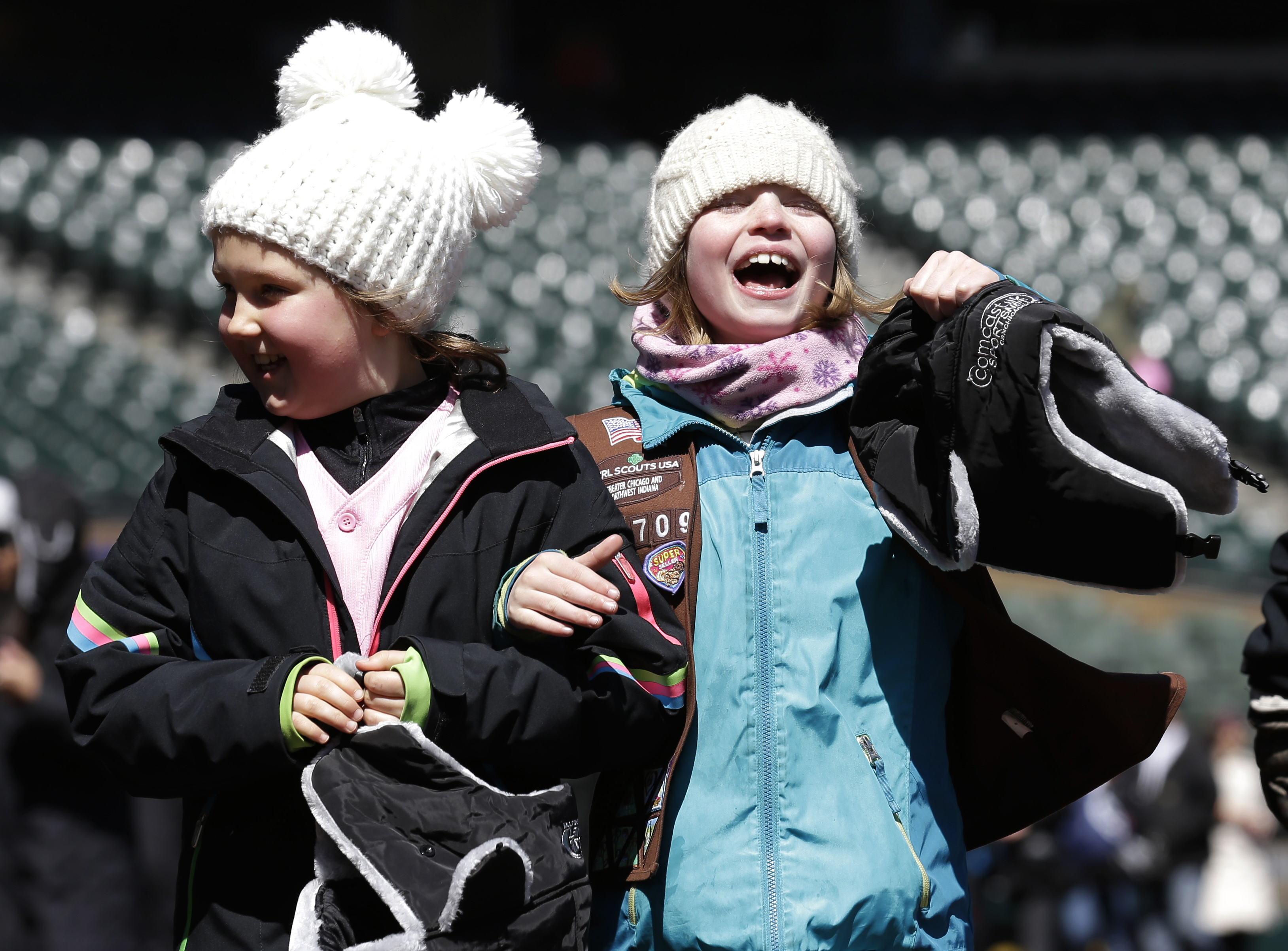 Fans bundle up as they walk on the field before a baseball game between the Chicago White Sox and the Cleveland Indians, Saturday, April 9, 2016, in Chicago. (AP Photo/Nam Y. Huh)
