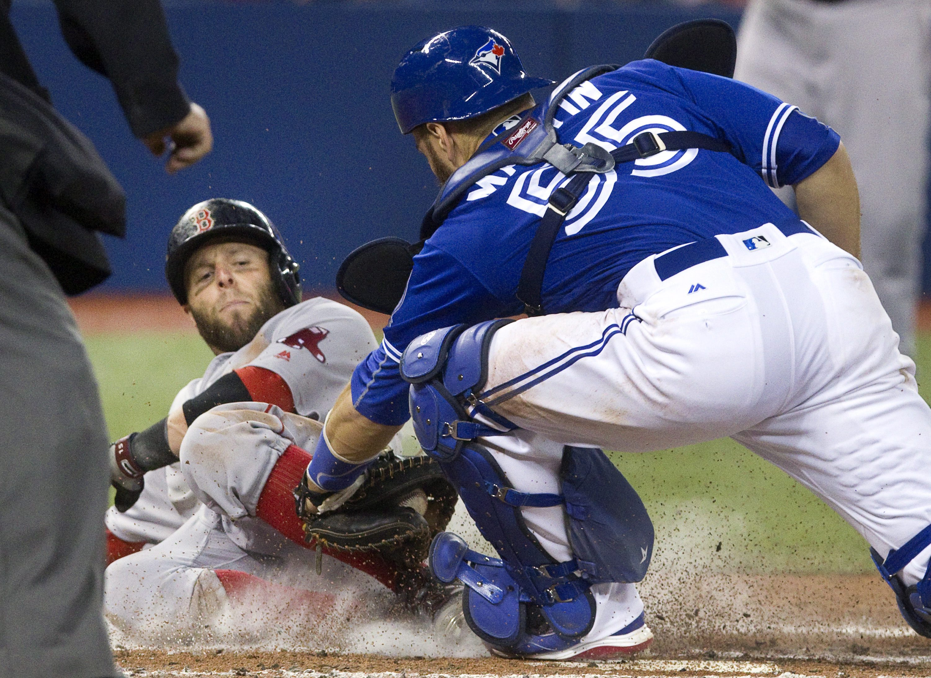 Boston Red Sox's Dustin Pedroia is out at home plate with the tag from Toronto Blue Jays catcher Russell Martin during third-inning baseball game action in Toronto, Sunday, April 10, 2016. (Fred Thornhill/The Canadian Press via AP) MANDATORY CREDIT